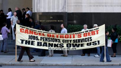 Protesters carry a sign outside the Levin Federal Courthouse in Detroit, Wednesday, July 24, 2013. Detroit's bankruptcy is hitting a courtroom for the first time as a judge considers what to do with challenges from retirees who claim their pensions are protected by the Michigan Constitution.