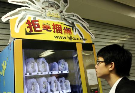A Chinese man looks at a crab vending machine at a subway station in Nanjing city, east Chinas Jiangsu province, 10 October 2010. Twin Lakes Crab Co., based in Gaoshun County roughly an hour-and-a-half drive south of the eastern Chinese city of Nanjing, recently unveiled what appears to be the worlds first live crab vending machine. The machine, installed in the Nanjing subway, sells crabs at prices ranging from 15 to 50 yuan (US$2.25 to US$7.5), depending on size. The crustaceans in question are hairy crabs, a regional specialty treasured throughout China and elsewhere for their roe. And since no one would dare eat hairy crab without ginger-infused vinegar, the bottom shelf offers bottles of that as well. The machine reportedly keeps the crabs, each packaged in its own custom-designed plastic cage, at 5 degrees Celsius, cold enough to put them to sleep but warm enough to keep them breathing. A sign next to the machine guarantees each crab will come out alive, offering compensation of three live crabs for every dead one that pops out.(Imaginechina via AP Images