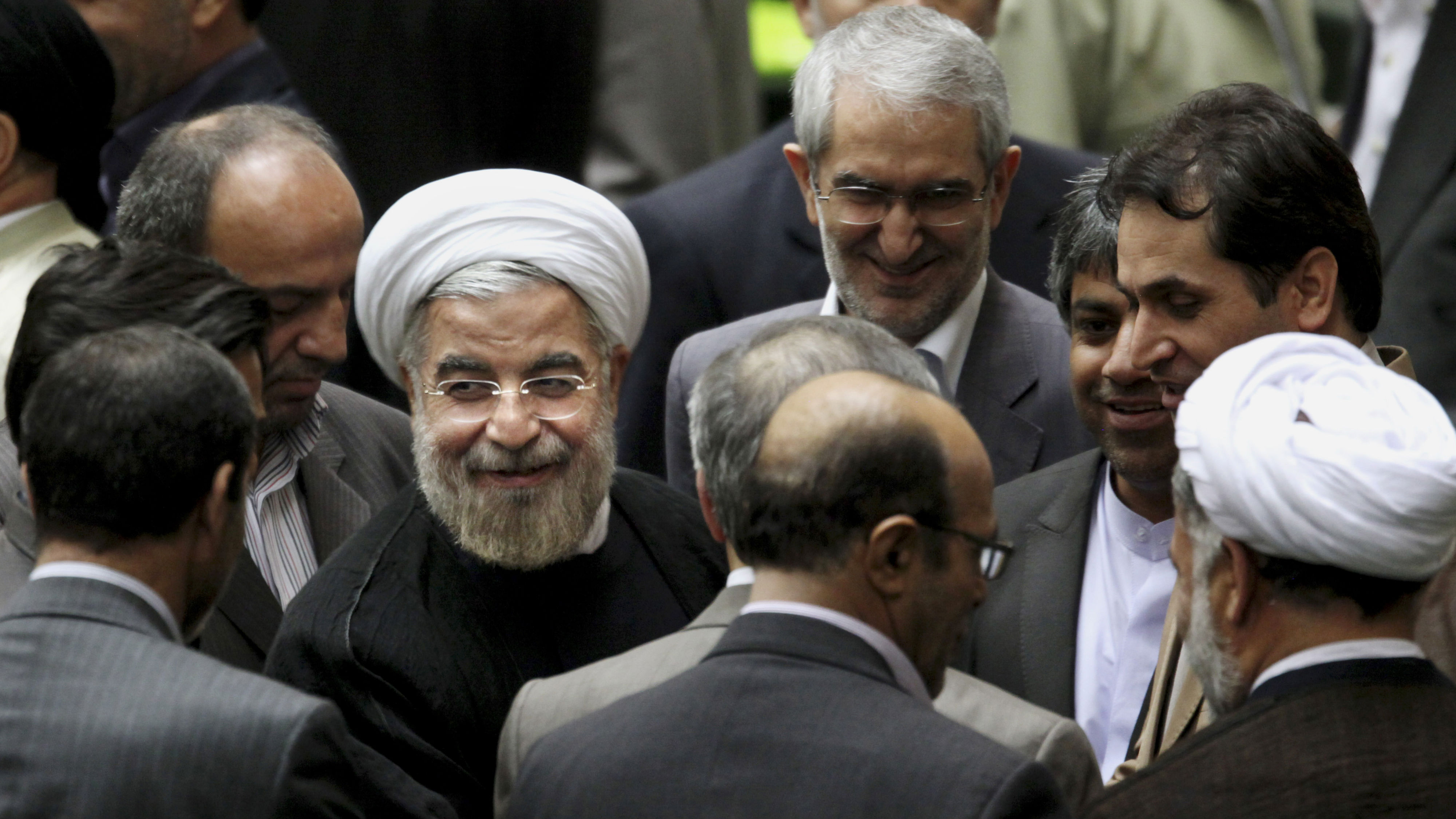 Iranian President Hasan Rouhani, center left with white turban, leaves at the conclusion of a session of the parliament to debate on his proposed Cabinet in Tehran, Iran, Tuesday, Aug. 13, 2013. In what is expected to be three days of debate ending Wednesday, legislators will vote individually to approve or reject each minister in Rouhani's 18-member Cabinet. (AP Photo/Ebrahim Noroozi)