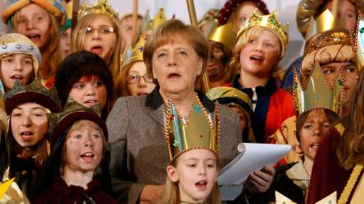 German Chancellor Angela Merkel (C) sings along with Sternsinger (carol singers) during a reception at the Chancellery in Berlin, January 4, 2013. Merkel annually receives children who take part in the Sternsinger project, collecting money for charity programs that help children in need around the world.