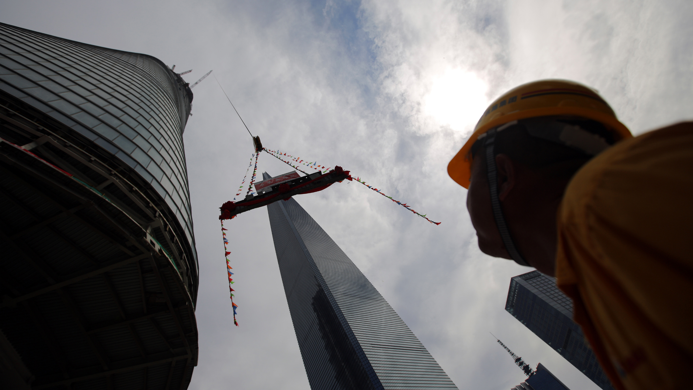 A worker looks a piece of steel lifted by a crane during the topping out ceremony at the Shanghai Tower, which is undergoing construction, at the financial district of Pudong in Shanghai August 3, 2013. The 632 metres (2,073 ft) high Shanghai Tower, which is scheduled to finish construction by the end of 2014, will be the tallest skyscraper in China and the second tallest in the world. REUTERS/Carlos Barria
