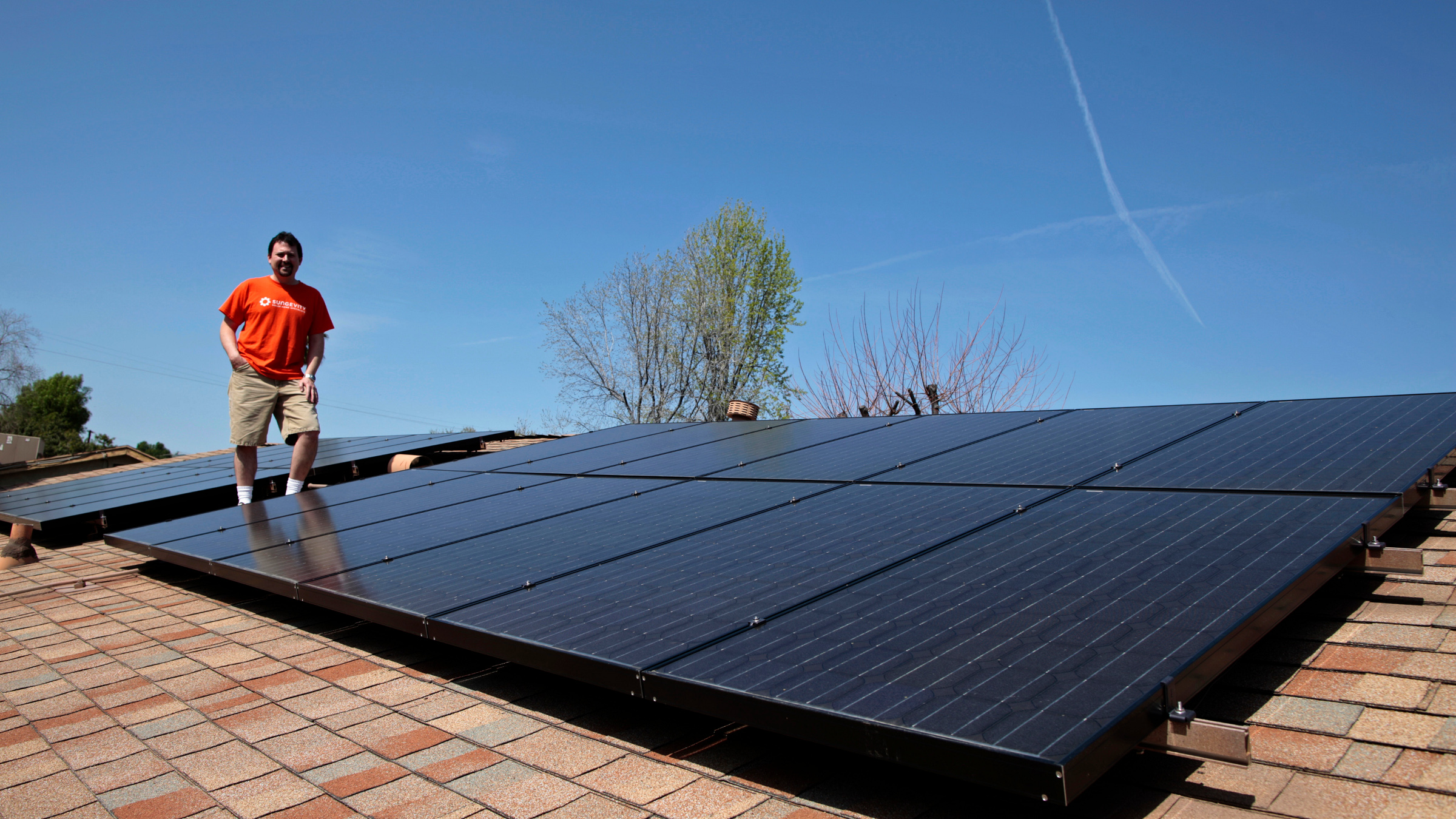 Mike Jones stands next to solar panels on the roof of his home in Los Angeles, California March 18, 2011. Jones leased 22 solar panels from solar electric system company Sungevity. The panels would have cost him $13,000, but the 20-year lease cost $4,000. The first month after the panels were installed Jones' electricity bill went down from $160 to $11.