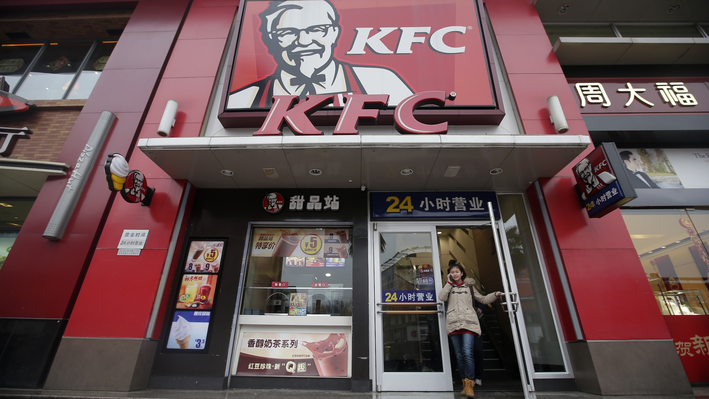 A woman walks out from a KFC restaurant as she speaks on her mobile phone in Wuhan, Hubei province, February 5, 2013. KFC parent Yum Brands Inc warned on Monday that it expects 2013 earnings to shrink rather than grow as it struggles to manage a food safety scare in China, and sees no return to growth in restaurant sales there until the fourth quarter. REUTERS/Stringer (CHINA - Tags: BUSINESS FOOD) CHINA OUT. NO COMMERCIAL OR EDITORIAL SALES IN CHINA - RTR3DD7F