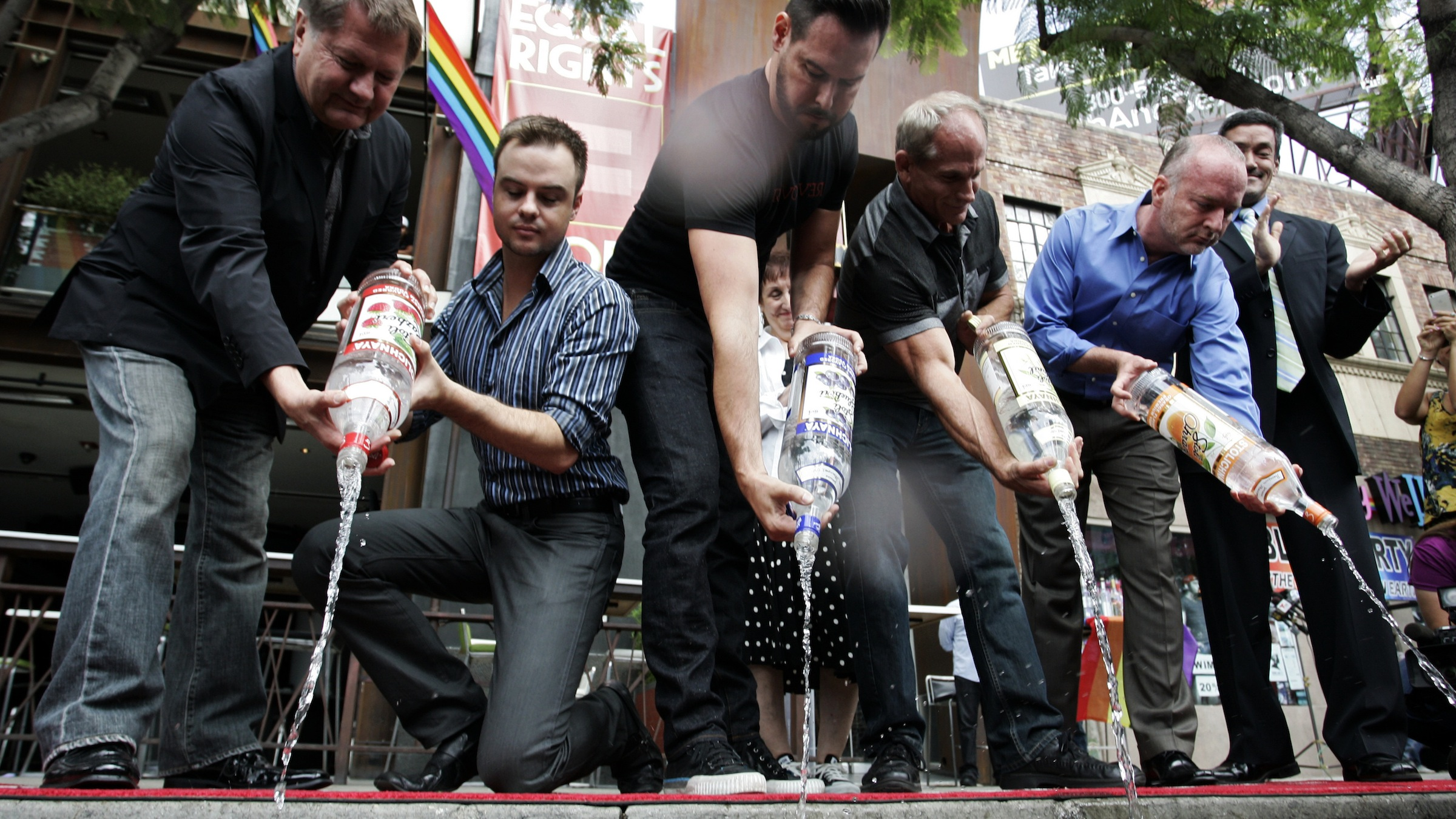 Michael Niemeyer (L-R), Matthew Ervin, Alfredo Diaz, Richard Grossi, Rodney Scott, and John Duran empty Russian vodka bottles filled with water, into the gutter during a news conference at Micky's nightclub in West Hollywood, California August 1, 2013. Bar owners, city officials and members of lesbian, gay, bisexual, and transgender (LGBT) organizations participated in the event to announce a boycott of Russian vodkas to protest new laws in Russia targeting homosexuals, according to a news release by the organizers. REUTERS/Jonathan Alcorn (UNITED STATES - Tags: POLITICS SOCIETY BUSINESS TPX IMAGES OF THE DAY) - RTX127LI