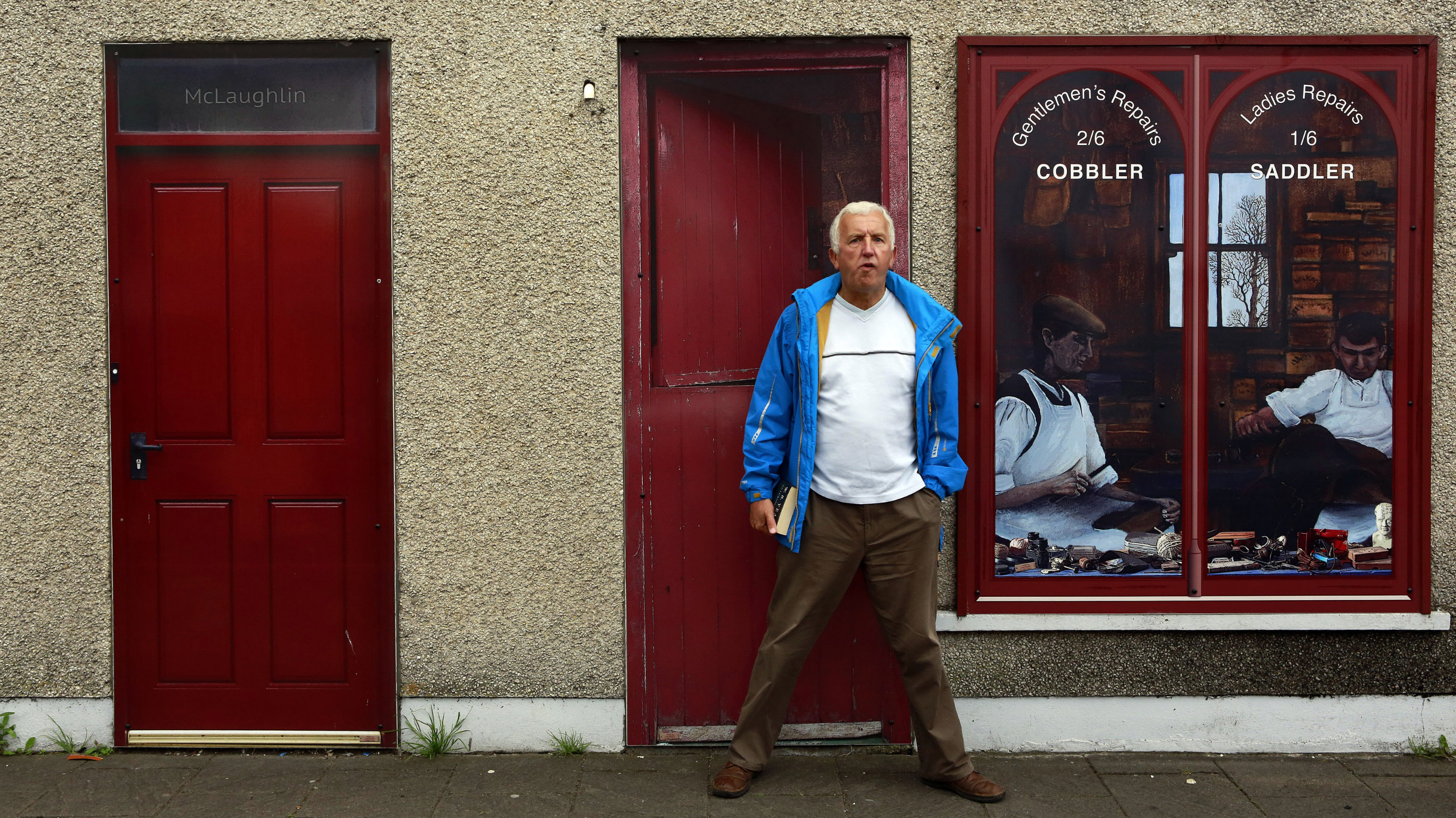 A man stands in front of an empty building, which has been covered with artwork to make it look more appealing, in the village of Bushmills on the Causeway Coast August 19, 2013. One of the homes of Irish whiskey has taken a scheme developed in Northern Ireland of erecting fake shop fronts where derelict buildings lie and has truly run with it in a bid to woo tourists. Bushmills, best known as the village where the whiskey of the same name was distilled for the first time 400 years ago, is now also becoming recognisable for the artwork and graphics that brighten up shop fronts left empty during the economic downturn.