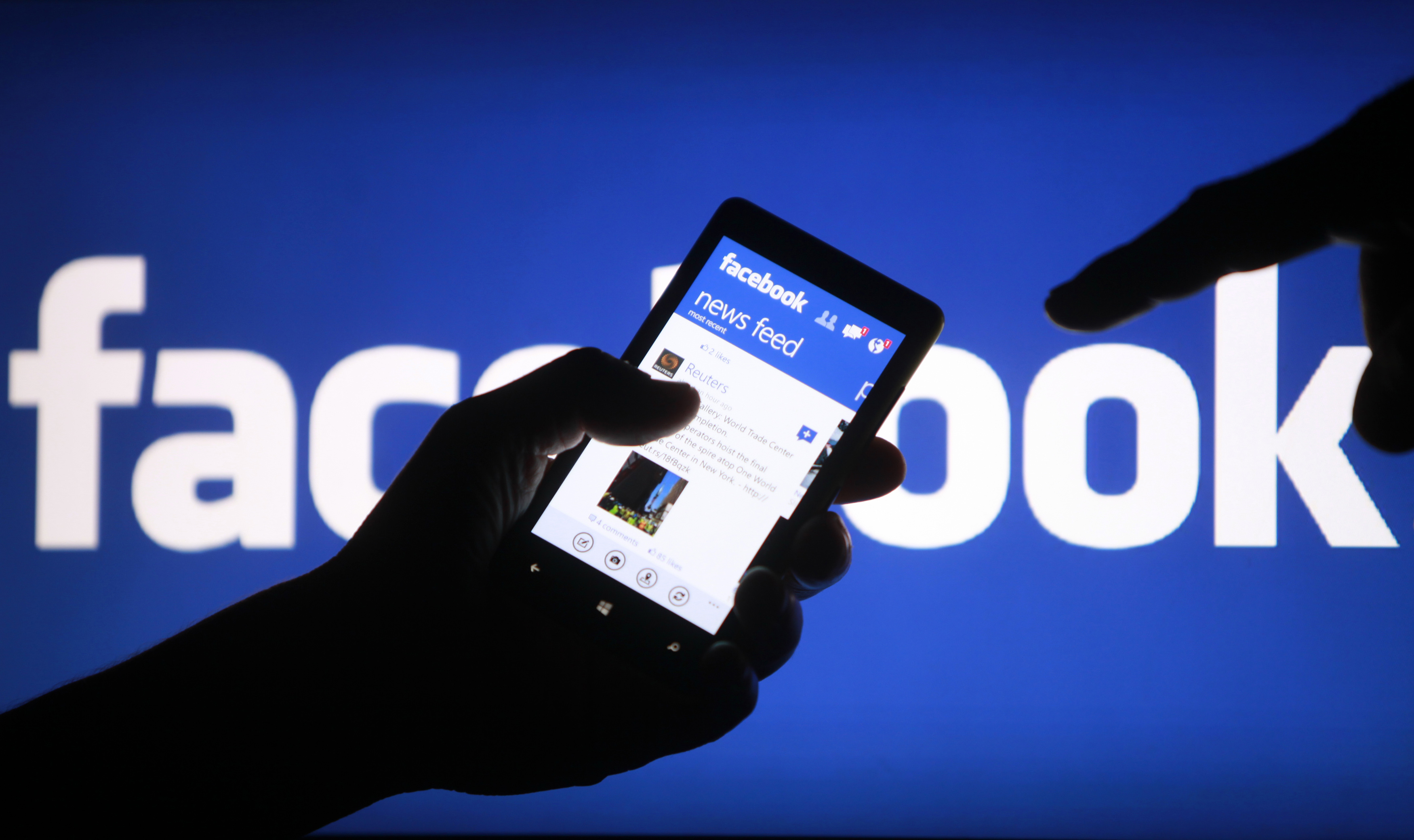 A smartphone user shows the Facebook application on his phone in the central Bosnian town of Zenica, in this photo illustration, May 2, 2013.  Facebook Inc's mobile advertising revenue growth gained momentum in the first three months of the year as the social network sold more ads to users on smartphones and tablets, partially offsetting higher spending which weighed on profits. REUTERS/Dado Ruvic (BOSNIA AND HERZEGOVINA - Tags: SOCIETY SCIENCE TECHNOLOGY BUSINESS) - RTXZ81J