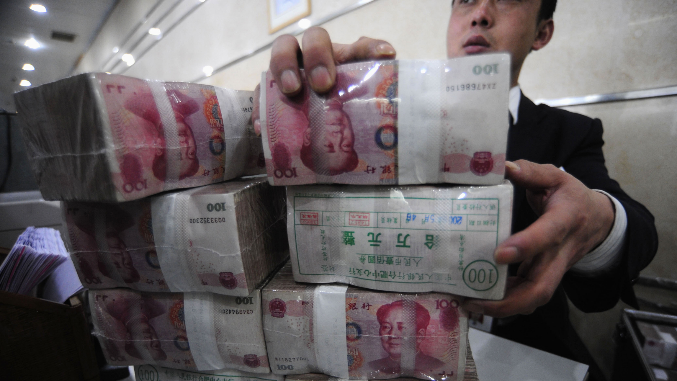 An employee packs bundles of Renminbi banknotes at a branch of Bank of China in Hefei, Anhui province February 8, 2010. China's central bank said on Monday that it plans to auction 40 billion yuan ($5.9 billion) of three-month finance ministry deposits to commercial banks on Thursday. REUTERS/Stringer