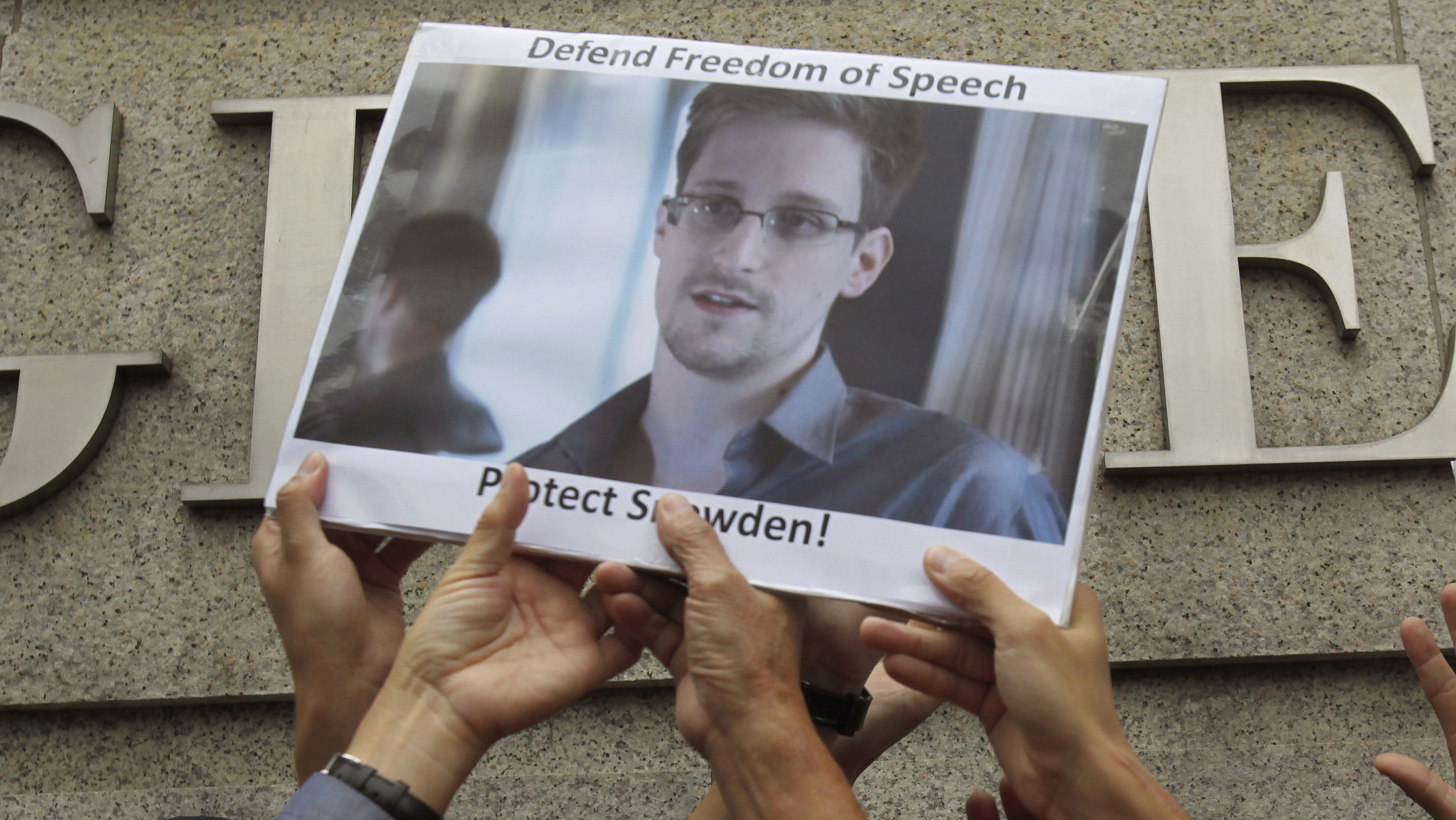 Photo of Edward Snowden being held aloft at a protest.