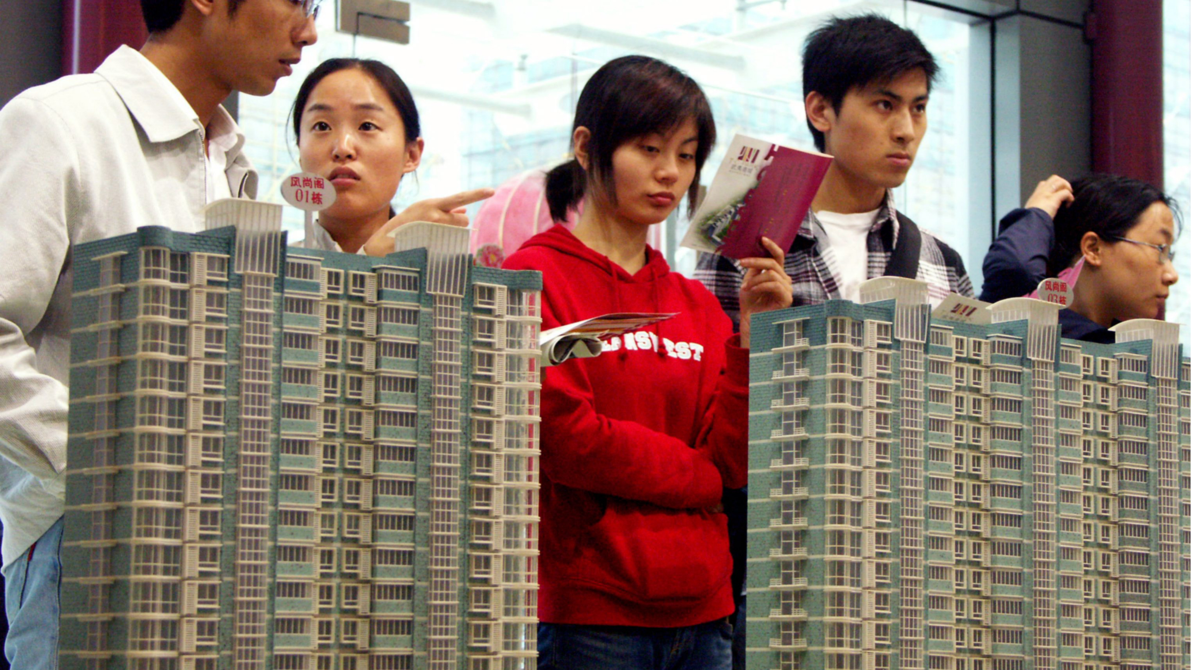 Chinese visitors look at model residential apartment buildings at a house fair in Nanjing city, east Chinas Jiangsu province, 8 April 2008. Chinese government on October 22 stepped in to bolster the ailing real estate market by lowering transaction taxes, reducing down payments and lowering mortgage rates. But analysts said the measures may not hold back price corrections because the current prices have surged far out of reach of many buyers. The Ministry of Finance and the central bank announced that property purchase tax would be lowered to 1 per cent for people buying their first home if it is smaller than 90sqm. The previous rate was 3 per cent, with those buying houses smaller than 140sqm paying 1.5 per cent. The new rate will be effective from November 1. For people buying their first home, the down payment ratio will be lowered to 20 per cent, and banks will be allowed to charge as low as 70 per cent of benchmark lending rates for such mortgages. Both measures are effective next Monday (October 27).(Imaginechina via AP Images