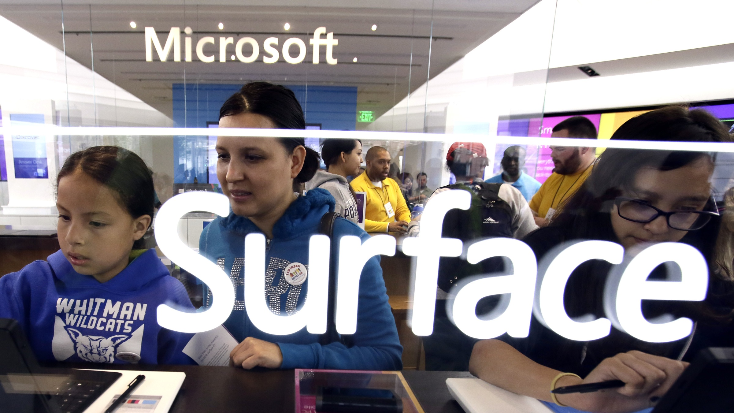 Natalie Andrade, left, 8, plays with a computer as mother Enedina Barrajas watches during the grand opening of a Microsoft retail store in downtown Portland, Ore., Thursday, June 20, 2013.(AP Photo/Don Ryan)