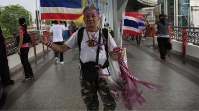 An elderly man sells flags and ribbons bearing the colors of the Thai national flag Wednesday, April 28, 2010 in Bangkok, Thailand. Pro-government supporters ended their rally at the Victory Monument early and have also suspended all further rallies indefinitely. (AP Photo/Wong Maye-E