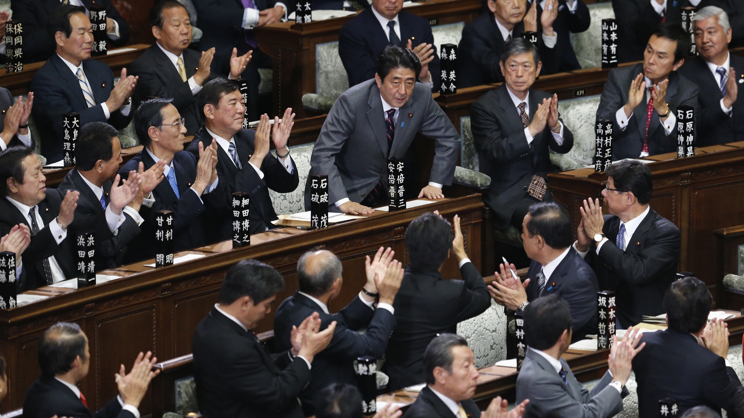 The leader of Liberal Democratic Party (LDP) Shinzo Abe (C) is applauded by his party members after being elected as Japan's Prime Minister at the Lower House of the Parliament in Tokyo December 26, 2012. The lower house of Japan's parliament approved Abe as prime minister on Wednesday, giving the hawkish lawmaker a second chance at the top job as the country battles deflation and confronts a rising China. REUTERS/Kim Kyung-Hoon