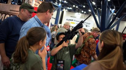 Family members watch as 11-year-old Mark takes aim with an AR-15 style assault rifle on the exhibit floor of the George R. Brown Convention Center, the site for the National Rifle Association (NRA)'s annual meeting in Houston, Texas on May 3, 2013. Tens of thousands of National Rifle Association members gather in Houston this weekend for the first time since the U.S. Senate rejected a plan last month to expand background checks for gun buyers, but officials say attendees will not sit back to celebrate victory. The family did not want to disclose their full name due to security concerns.