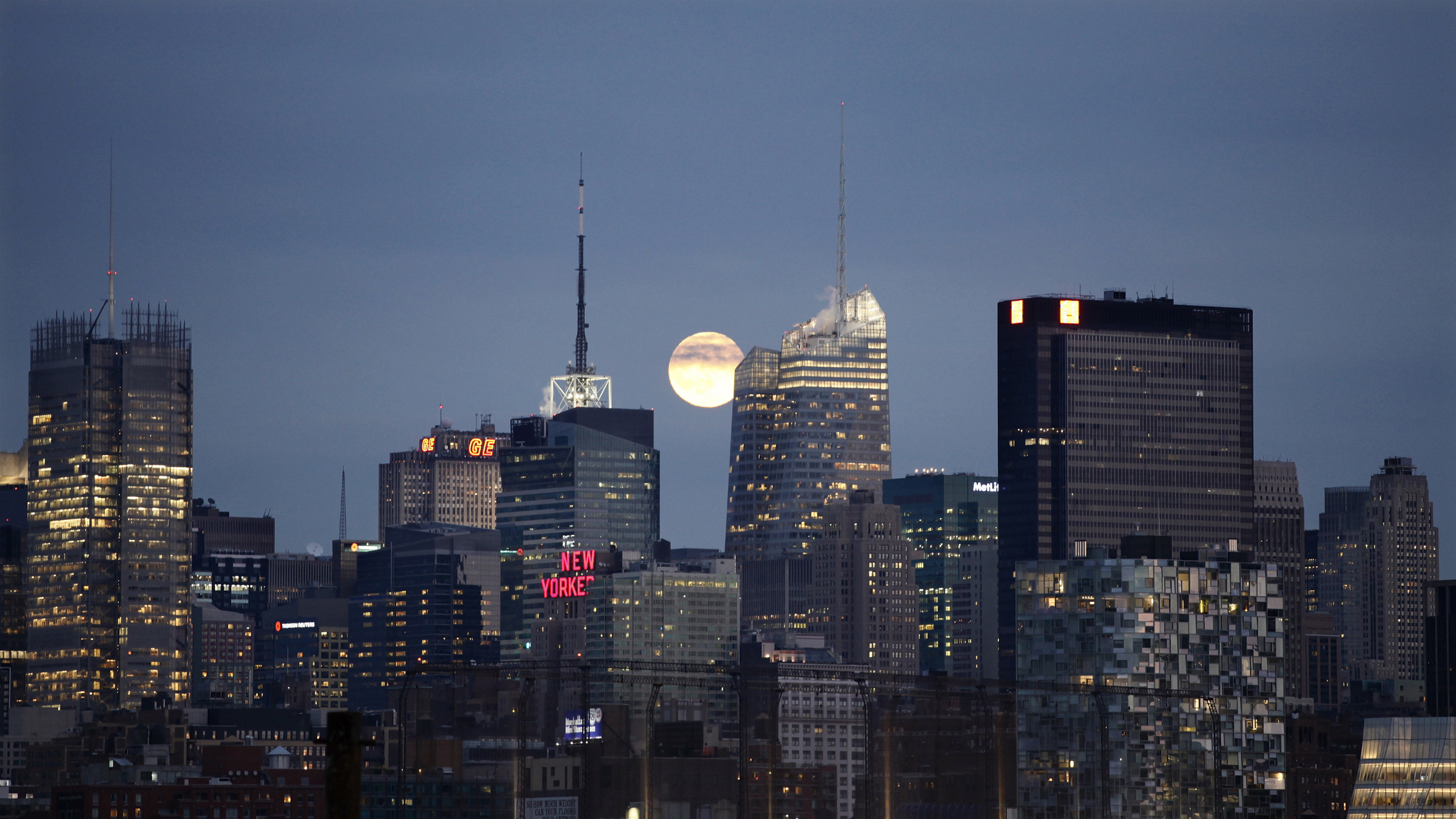A full moon rises behind the skyline of midtown Manhattan in New York, November 21, 2010. The New York Times building sits at left and the new Bank of America tower is in the center, in front of the moon. REUTERS/Gary Hershorn