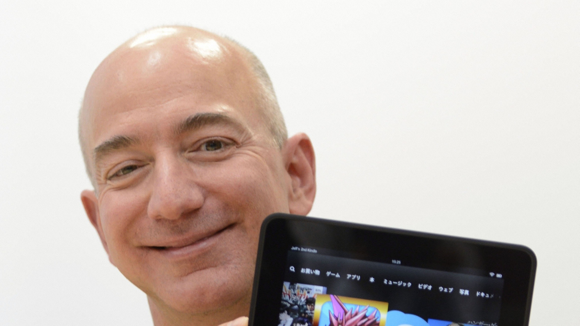 TOKYO, Japan - Amazon.com Inc. chief executive officer Jeff Bezos holds a Kindle Fire HD in Tokyo on Oct. 24, 2012. The U.S. online retailer said the same day it will start selling Kindle electronic books and readers in Japan. (Kyodo via AP Images)