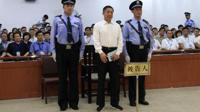 In this photo released by the Jinan Intermediate People's Court, Bo Xilai, center, who was tried last month on charges of taking bribes, embezzlement and abuse of power, stands inside the court in Jinan, in eastern China's Shandong province, Sunday, Sept. 22, 2013. The Chinese court convicted the fallen politician of corruption and sentenced him to life in prison. (AP Photo/Jinan Intermediate People's Court