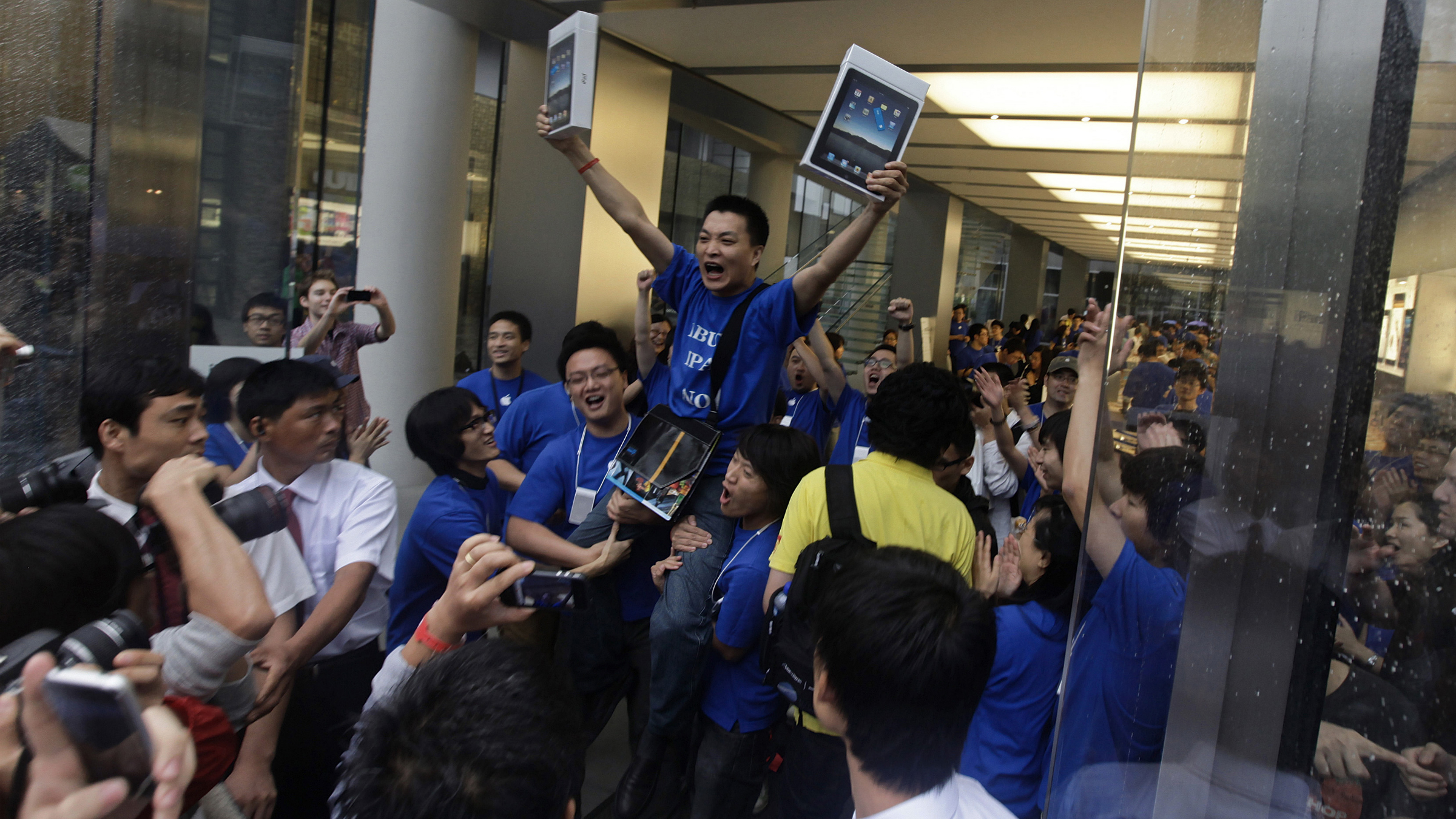 Customer Han Ziwen holds up his iPads at an Apple flagship store in Beijing, September 17, 2010. Han is one of the first customers to officially buy an iPad in Chinese mainland after queueing more than 60 hours. Apple officially launches its era-defining product in the Chinese mainland on Friday. REUTERS/Petar Kujundzic