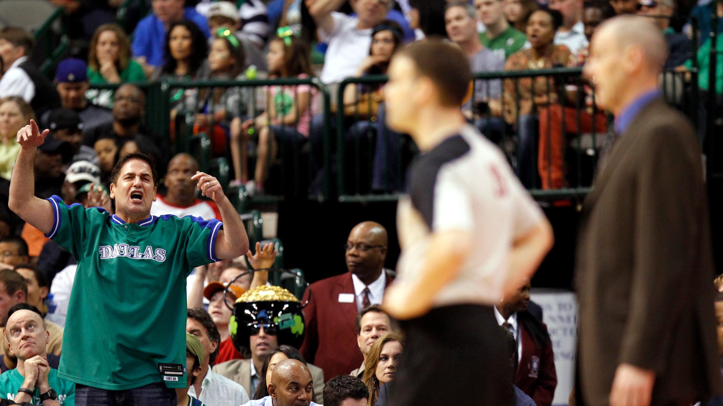 Dallas Mavericks owner Mark Cuban reacts as Oklahoma City Thunder head coach Rick Carlisle (R) watches during the second half of their NBA basketball in Dallas, Texas March 17, 2013.