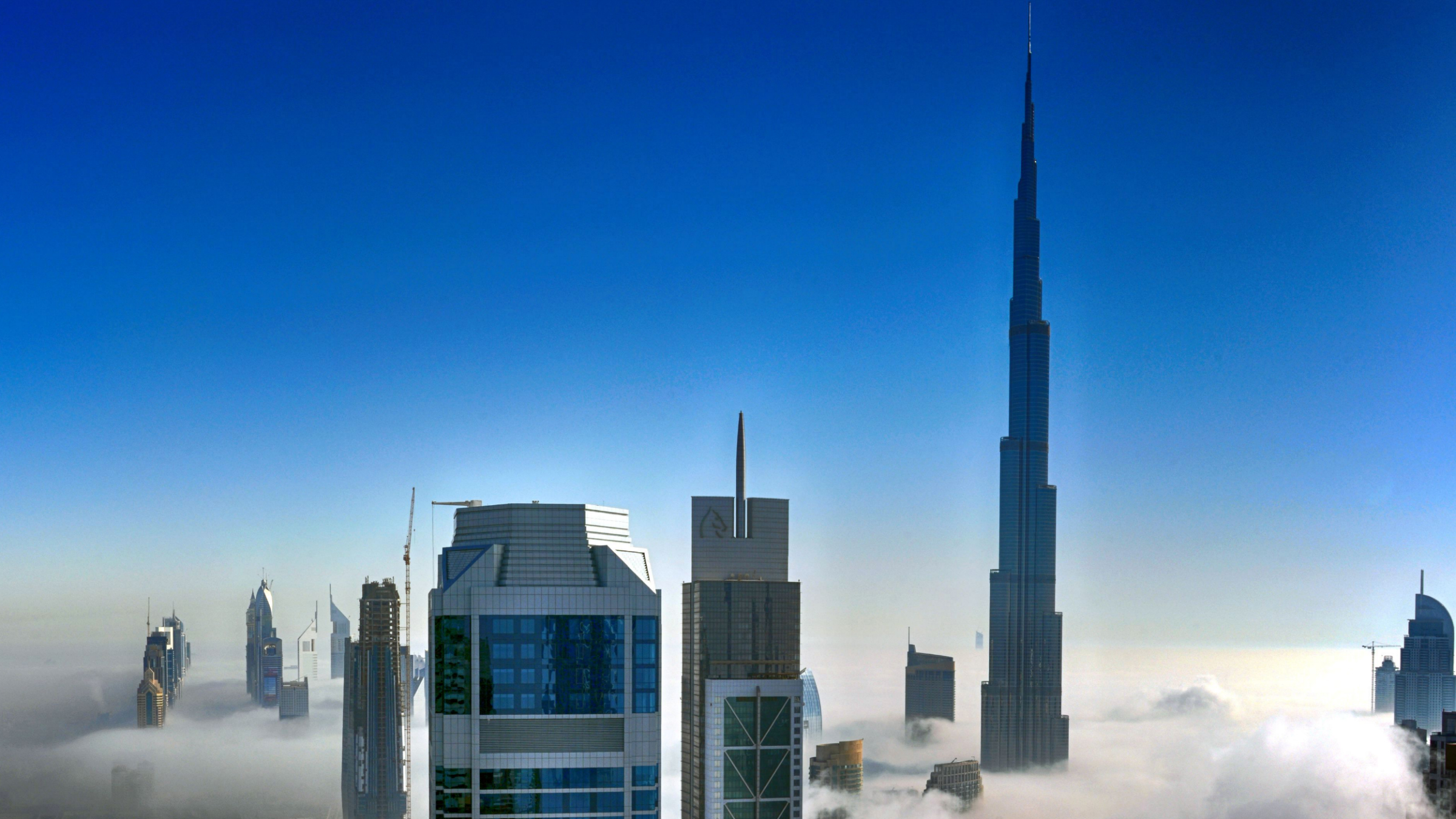 """Beautiful Blanket Of Fog Covers Dubai Residents in these high-rise blocks really do have their heads in the clouds - as the top of their buildings can just be seen poking out above a thick fog. Photographer Shiva Menon snapped the Dubai skyline from above the fog in his apartment on the 52nd floor of the MBK Tower. But the bed of fog was so dense it was impossible to see the horizon or even ground below. Instead, the tops of the buildings in the downtown Business Bay area - including the luxury Burj Al Arab hotel - appear to rise eerily from the fog. Many of the buildings are still under construction. Shiva, 37, from Dubai, took the photographs at around 7.30am before the early morning mist had a chance to clear. He said: """"The sea of mist was caused by a natural phenomena. """"Every year around this time the temperature begins to drop and humidity meets cooler air, forming the 'rolling fog'. """"As the sun rises it burns away the mist to reveal the desert once again. """"The thick white fog develops overnight as a result of the disparity between high temperatures and humidity during the day and the drop of the mercury during the night."""" The fog - which floats around 30 metres above the ground - is only this thick on a few days each year, usually between September and November. However, on other days it is still """"prominent"""" enough to affect visibility and traffic in the Emirate state. Shiva added: """"I was able to capture the scene with its actual essence, serenity and uniqueness. """"It was totally surreal and felt like I was in a completely different galaxy. """"It was quiet mesmerizing and a very calmly experience. A very gorgeous scene."""""""