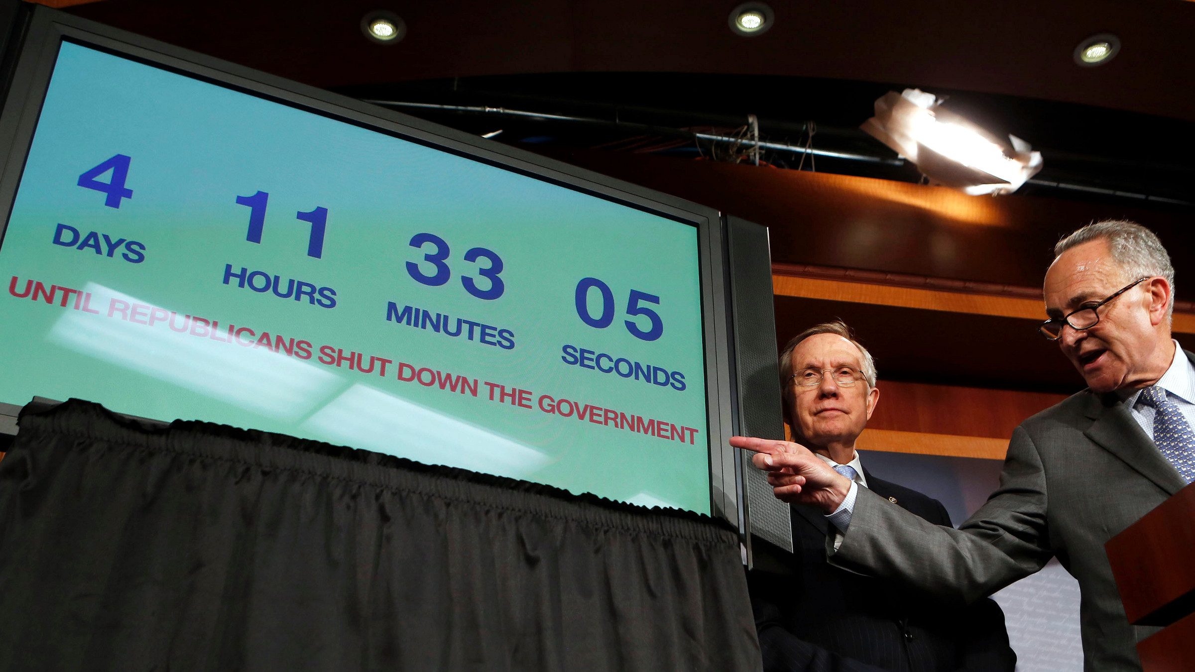 """U.S. Senate Majority Leader Harry Reid (L) and Senator Charles Schumer stand next to a countdown clock while they discuss the potential U.S. government shutdown in four days, on Capitol Hill in Washington September 26, 2013. Reid, a Democrat, on Thursday rejected plans by Republicans in the House of Representatives to advance a debt limit increase bill that contains measures such as delaying """"Obamacare."""""""