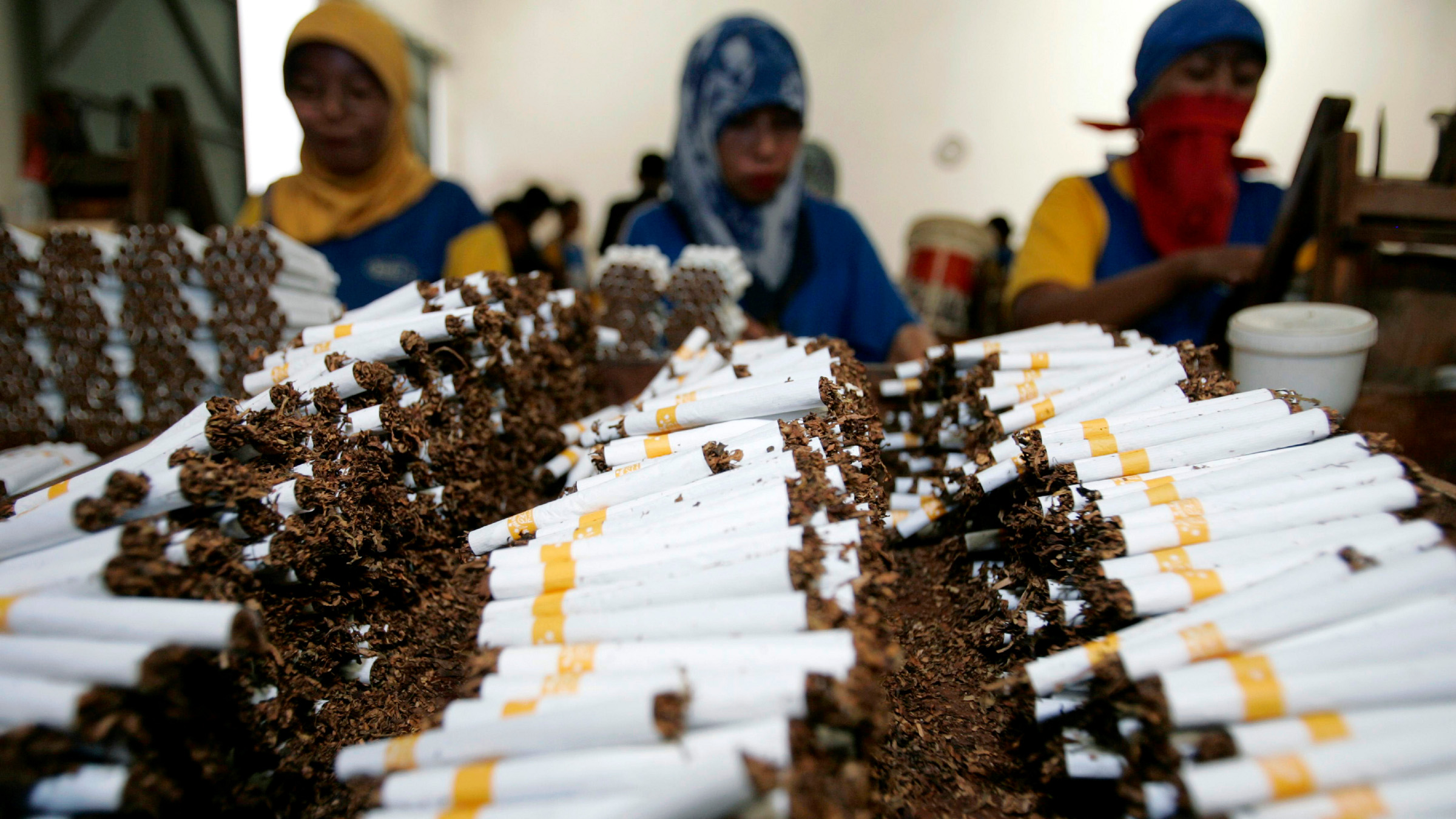 Workers roll cigarettes in a factory in Sidoarjo, East Java province February 2, 2009. The company's production manager said on Monday that the production of cigarettes has decreased after Indonesia's Ulema Council (MUI) issued a fatwa prohibiting smoking in public places and by pregnant women and children. Indonesian smokers and the country's tobacco industry have slammed a move by the nation's top Islamic body to place restrictions on tobacco use by Muslims, calling it an interference in private lives. Health campaigners welcomed the move, but said the government now needed to do more if there was to be any impact on curbing smoking in the world's fifth largest tobacco market.