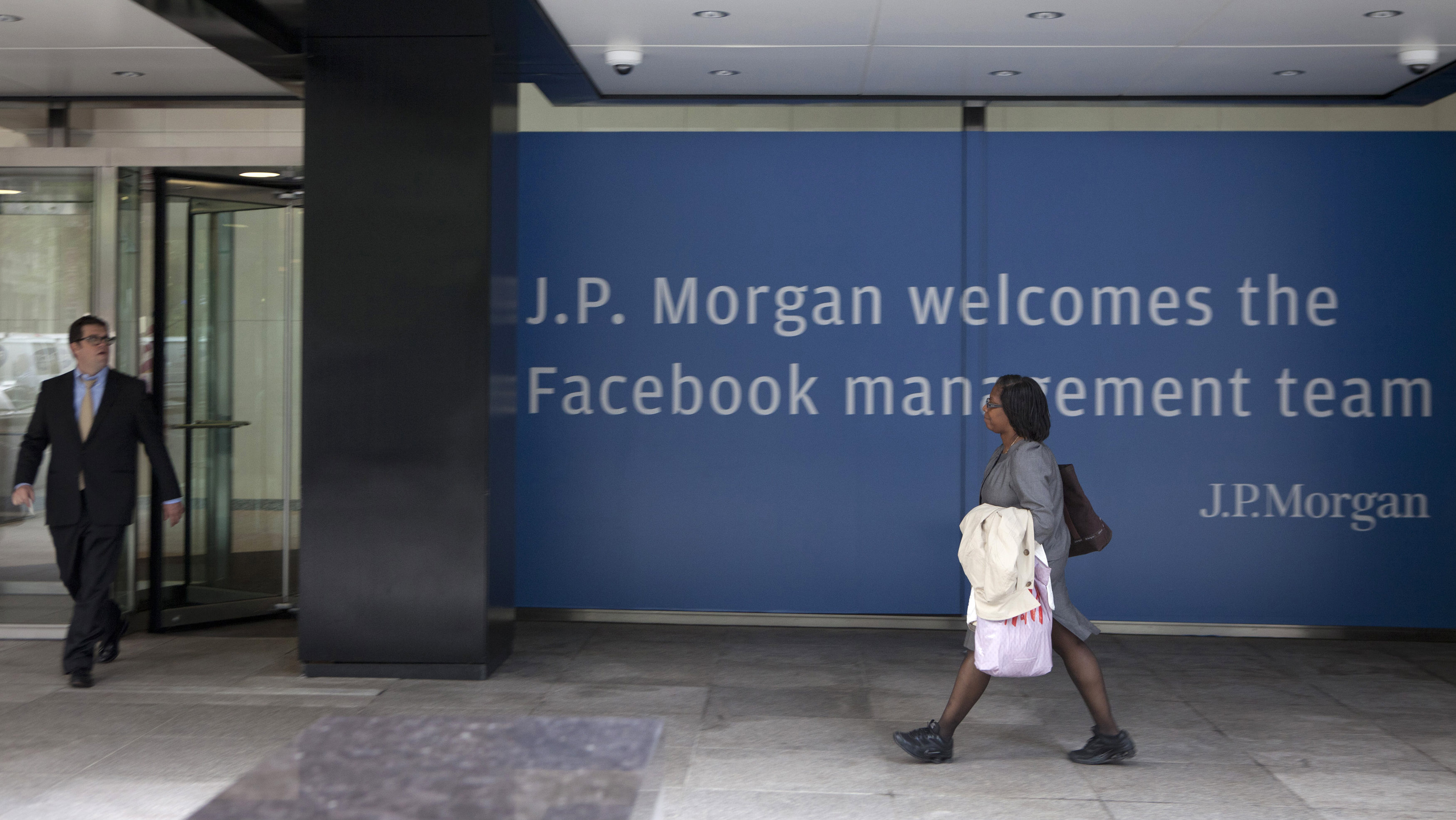 People walk near a sign welcoming the IPO of Facebook outside the offices of J.P. Morgan in New York City, New York, May 4, 2012. Facebook Inc aims to raise about $10.6 billion in Silicon Valley's largest IPO, dwarfing the coming-out parties of tech companies like Google Inc and granting the world's largest social network a market value close to Amazon.com's. REUTERS/Lee Celano