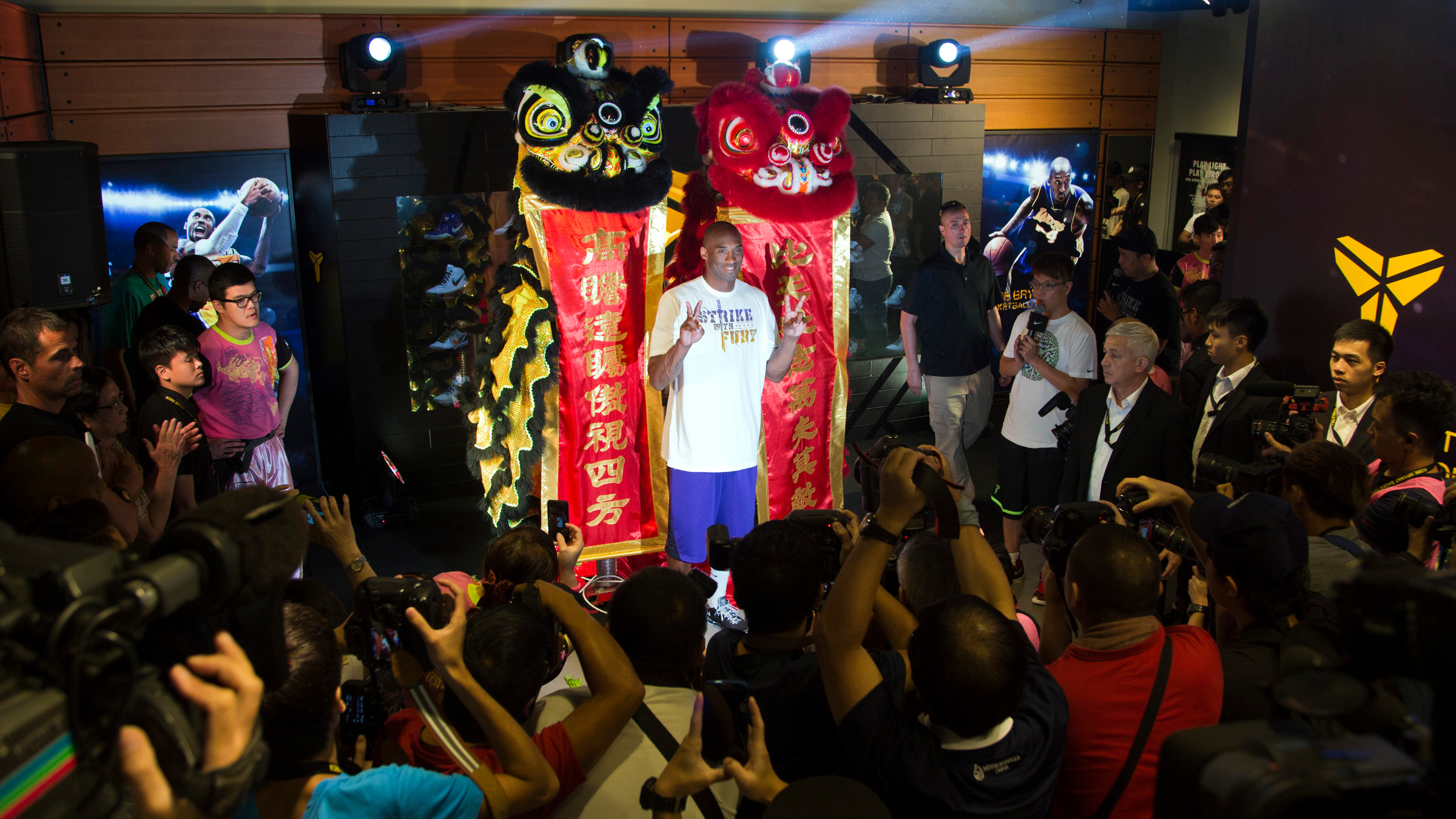 Los Angeles Lakers NBA star Kobe Bryant poses in front of dancers wearing traditional Chinese lion dance costumes while attending an opening of a new Nike store in Hong Kong's Mongkok district August 3, 2013. Bryant kicks off his China tour in Hong Kong, where he meets fans and gives a few pointers to local teenage basketball players.