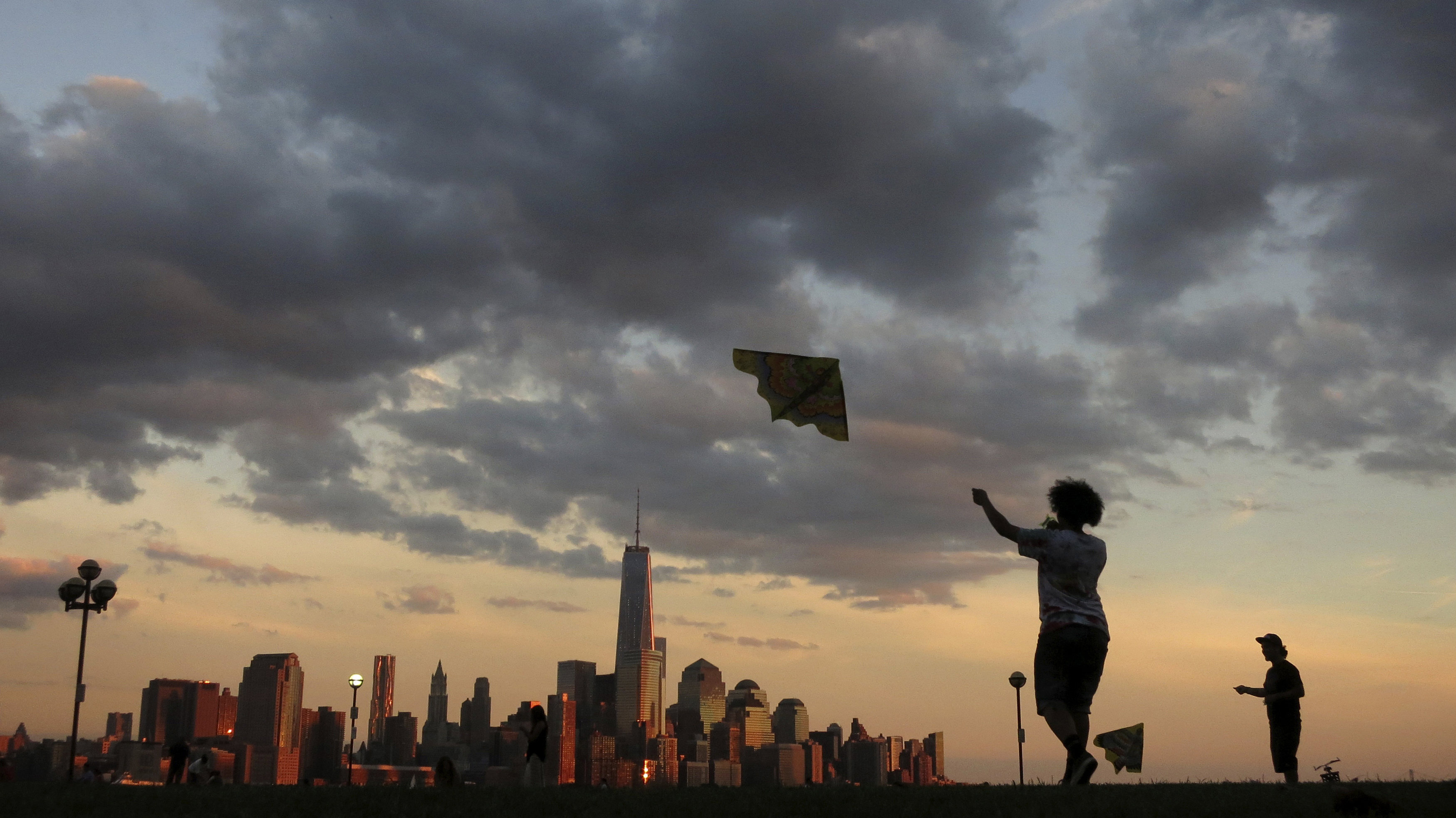 New York's Lower Manhattan skyline is seen the distance as a women flies a kite in a park along the Hudson River in Hoboken, New Jersey September 3, 2013. New York City is iconic in any weather, but the warm season adds a special flavour to its bustling streets, leafy parks and world-famous skyline. The summer is about to draw to a close, as fall begins in the northern hemisphere with the Autumnal Equinox on September 22. Picture taken September 3, 2013.