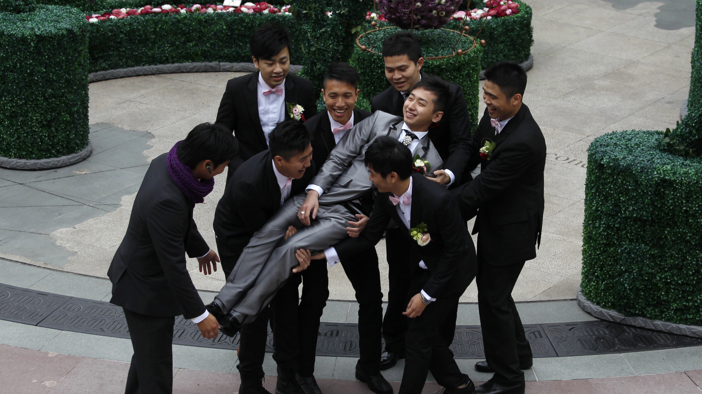 A bridegroom is carried by his friends during his wedding celebration on Valentine's Day in Hong Kong February 14, 2011. REUTERS/Bobby Yip