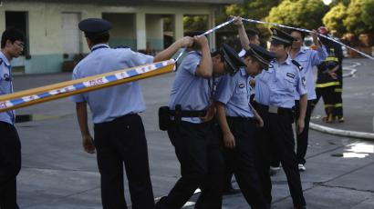 Policemen through a cordon at an entrance of a refrigeration unit of Shanghai Weng's Cold Storage Industrial Co. Ltd. in the Baoshan district of Shanghai August 31, 2013. A liquid ammonia leak from the refrigeration unit at the cold storage facility in Shanghai on Saturday has killed 15 people and injured 26 others, local authorities said. The leak occurred at 10:50 am local time (0250 GMT) at Shanghai Weng's Cold Storage Industrial Co. Ltd., located in the Baoshan district of eastern Shanghai, the Shanghai municipal government said on its official Sina Weibo account. REUTERS/Aly Song