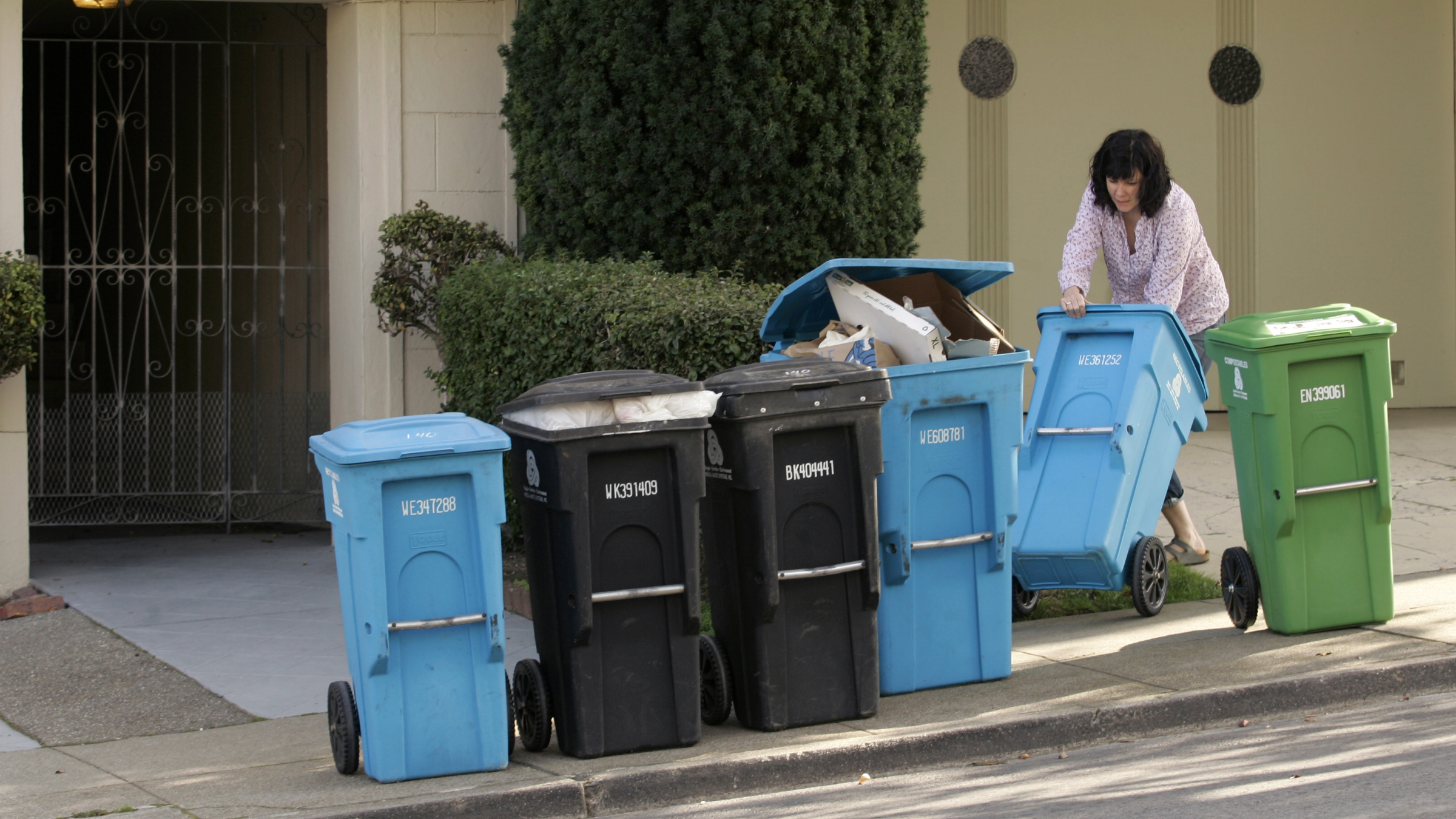 A resident wheels a recycling container to the curb for pickup in San Francisco, California November 4, 2009. Most of the city's recycled refuse is taken to Recology at Pier 96, where glass, plastic and paper is sorted and compressed into compact cubes. Picture taken November 4, 2009. REUTERS/Robert Galbraith