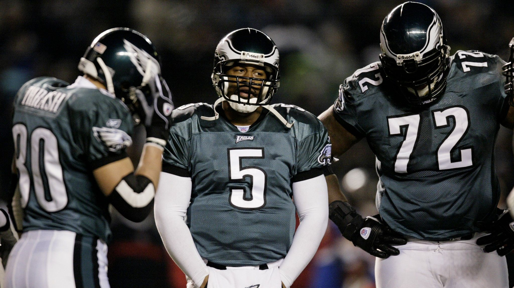 Philadelphia Eagles quarterback Donovan McNabb's (5) expression and body language illustrate what kind of day he is having against the Tampa Bay Buccaneers during their NFC Championship game in Philadelphia, January 19, 2003. Surrounding McNabb are teammates James Thrash (80) and Tra Thomas (72). REUTERS/Mike Segar  GAC - RTR11JVO