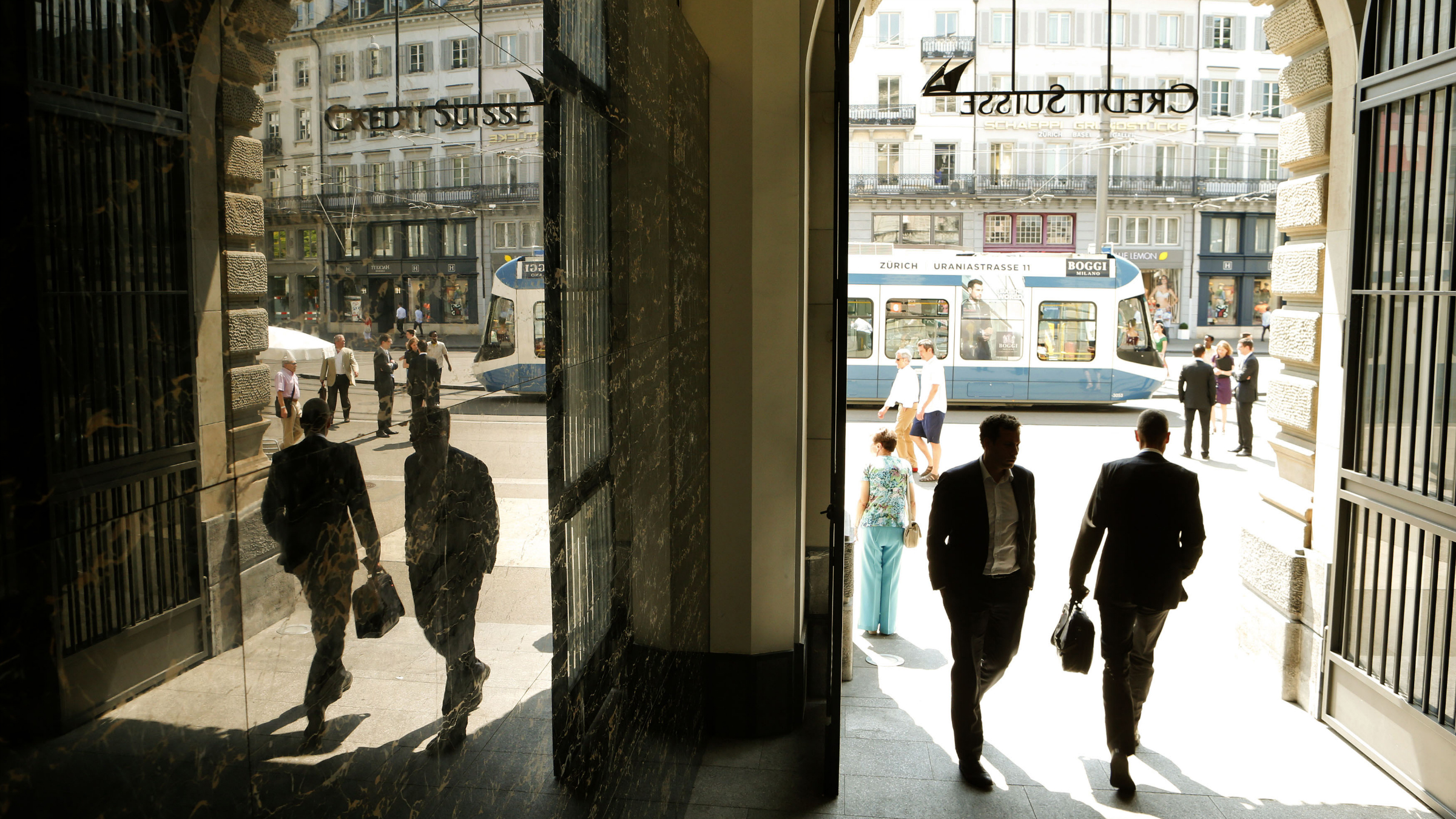 People walk through the entrance of the headquarters of Swiss bank Credit Suisse at the Paradeplatz square in Zurich July 25, 2013. Credit Suisse's investment bank drove a one-third jump in second-quarter group earnings, while higher interest rates should help future profits at its private bank, the lender said on Thursday. The Zurich-based bank's normally stable wealth management arm has been rattled by a global crackdown on Swiss bank secrecy with European clients withdrawing money to avoid being snared by tax-evasion probes. REUTERS/Arnd Wiegmann