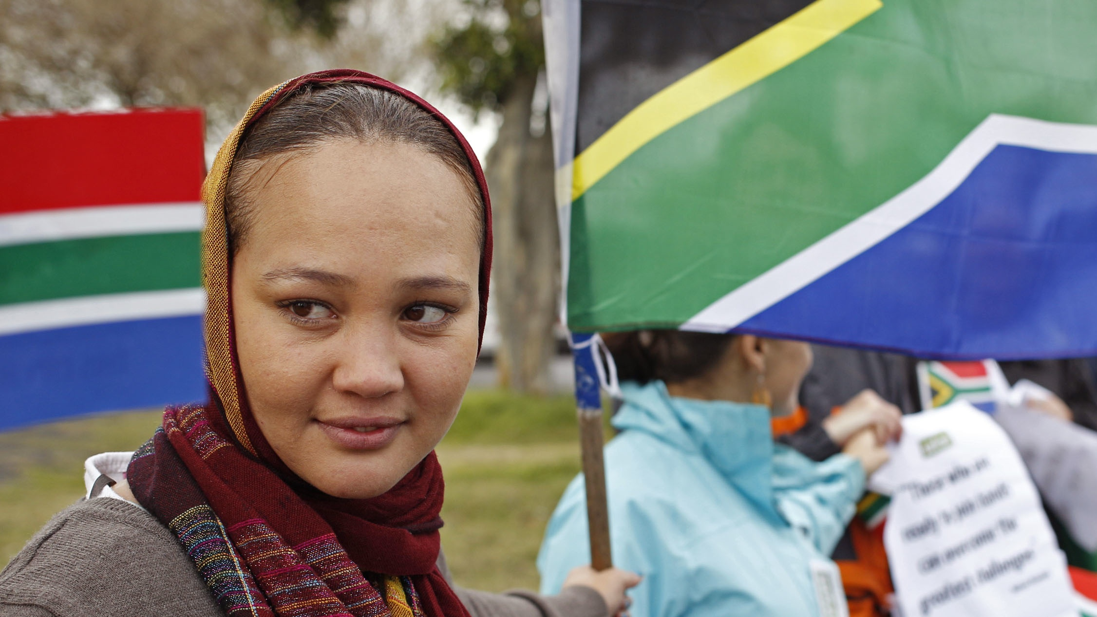 The South African flag, next to a woman, as she and others celebrate former South African President, Nelson Mandela's 95th birthday by forming a human chain in Cape Town, South Africa, Thursday, July 18, 2013. South Africa celebrated his birthday on Thursday, a milestone capped by news that the former president's health was improving after fears that he was close to death during ongoing hospital treatment. (AP Photo/Schalk van Zuydam)