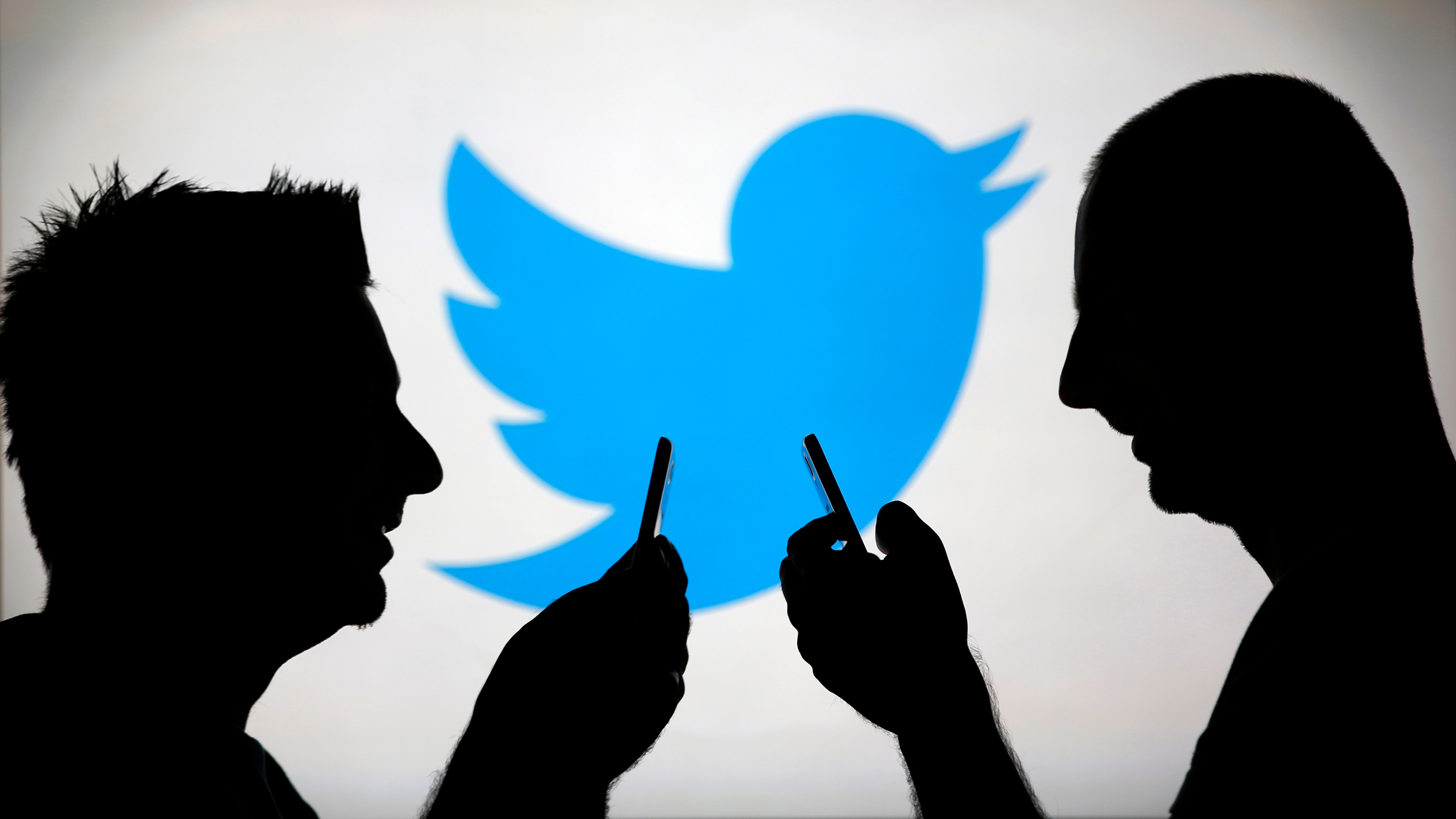 Men are silhouetted against a video screen with a Twitter logo as he poses with a Samsung S4 smartphone in this photo illustration taken in the central Bosnian town of Zenica, August 14, 2013.