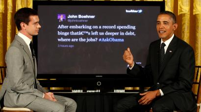 U.S. President Barack Obama talks about a tweet from U.S. Speaker of the House John Boehner on a screen behind him during his first ever Twitter Town Hall in the East Room at the White House in Washington, July 6, 2011. Joining the president at left is Twitter co-founder Jack Dorsey.