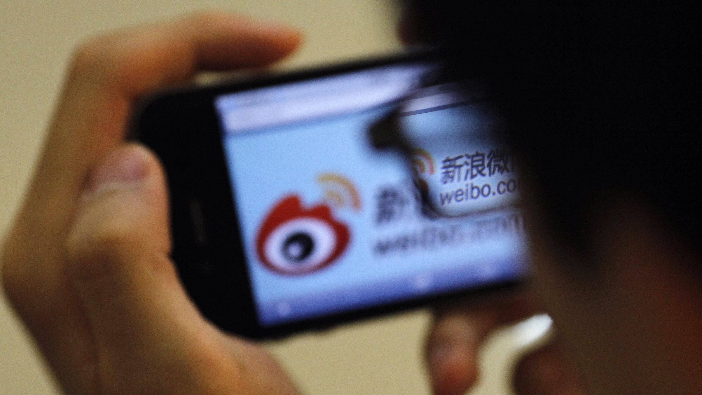DATE IMPORTED:May 29, 2012A man holds an iPhone as he visits Sina's Weibo microblogging site in Shanghai May 29, 2012. China's Sina Corp has introduced a code of conduct for users of the local version of Twitter amid accusations of censorship to rein in what has grown into a raucous online forum to air political and social grievances. The code of conduct, first announced earlier this month, stipulates that users of Sina's Weibo microblogging site cannot post information that is against the principles of the constitution, cannot harm national unity, disclose state secrets or publish false information, among other rules. REUTERS/Carlos Barria