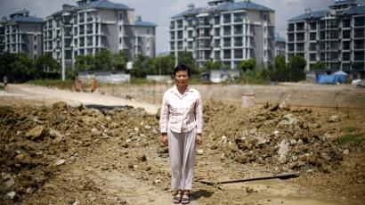 Xu Haifeng poses at a construction site area where her house stood in Wuxi, Jiangsu province, August 20, 2013. When Xu's home was razed three years ago, she went to China's capital Beijing to complain about the city and county governments that ordered the demolition. Since then she says family members have been kidnapped at least 18 times, typically having black bags thrust over their heads before being taken to a hotel-turned-illegal jail in the eastern city of Wuxi and locked for weeks in a tiny, windowless room. Xu's story is shocking even in a country that has become used to tales of arbitrary and sometimes violent land expropriations. It illustrates how the stresses from the deep indebtedness of China's local governments extend beyond banks into the lives of ordinary Chinese, as hard-up authorities resort to any means they can in a desperate scramble for funds. Picture taken August 20, 2013. REUTERS/Carlos Barria