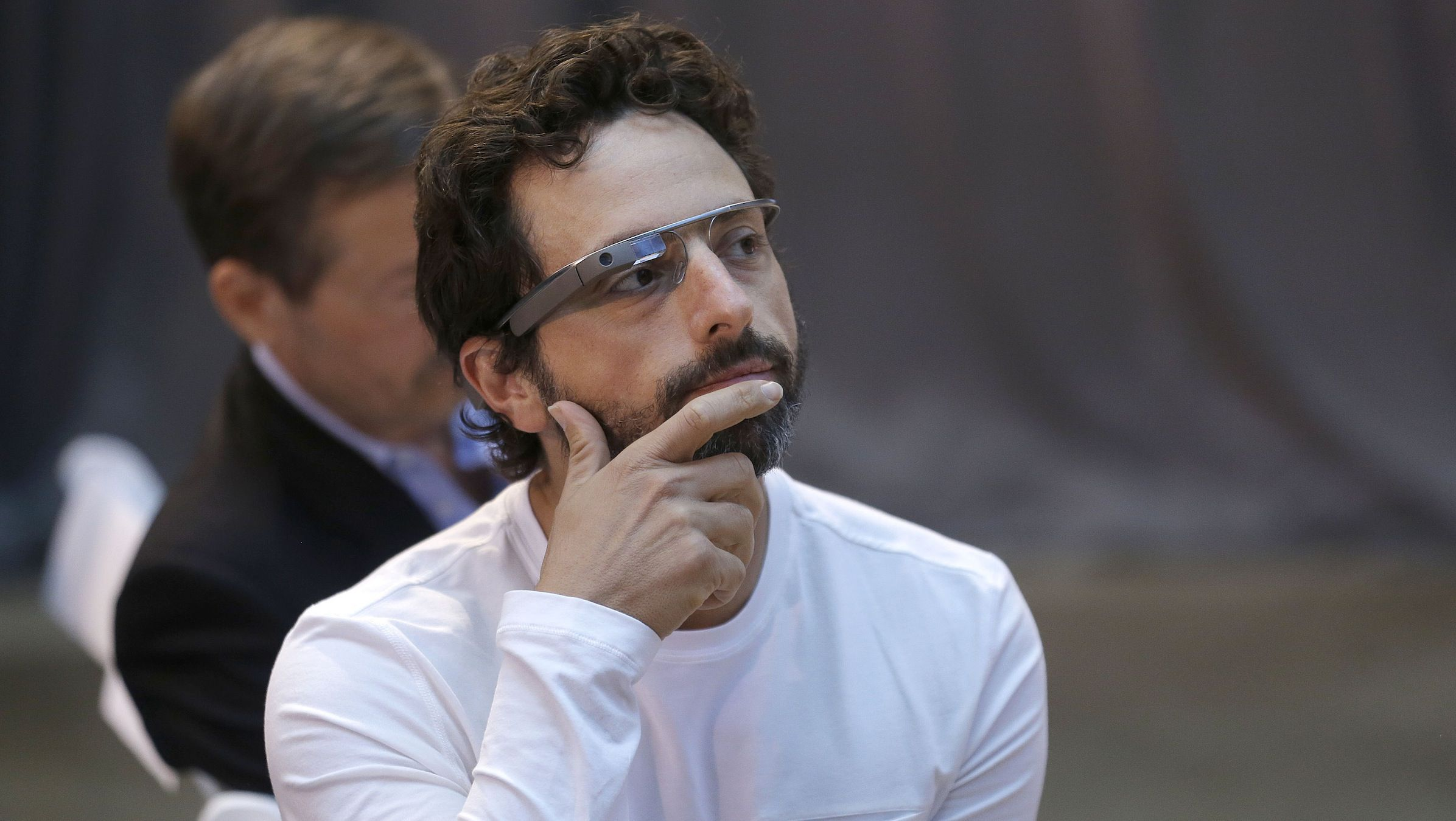 """Google co-rounder Sergey Brin wears Google Glass glasses at an announcement for the Breakthrough Prize in Life Sciences at Genentech Hall on UCSF's Mission Bay campus in San Francisco, Wednesday, Feb. 20, 2013. Google is giving more people a chance to pay $1,500 for a pair of the Internet-connected glasses that the company is touting as the next breakthrough in mobile computing. The product, dubbed """"Google Glass,"""" will be offered to """"bold, creative individuals"""" selected as part of a contest announced Wednesday. Participants must live in the U.S. and submit an application of up to 50 words explaining what they would do with the Google Glass technology. (AP Photo/Jeff Chiu)"""