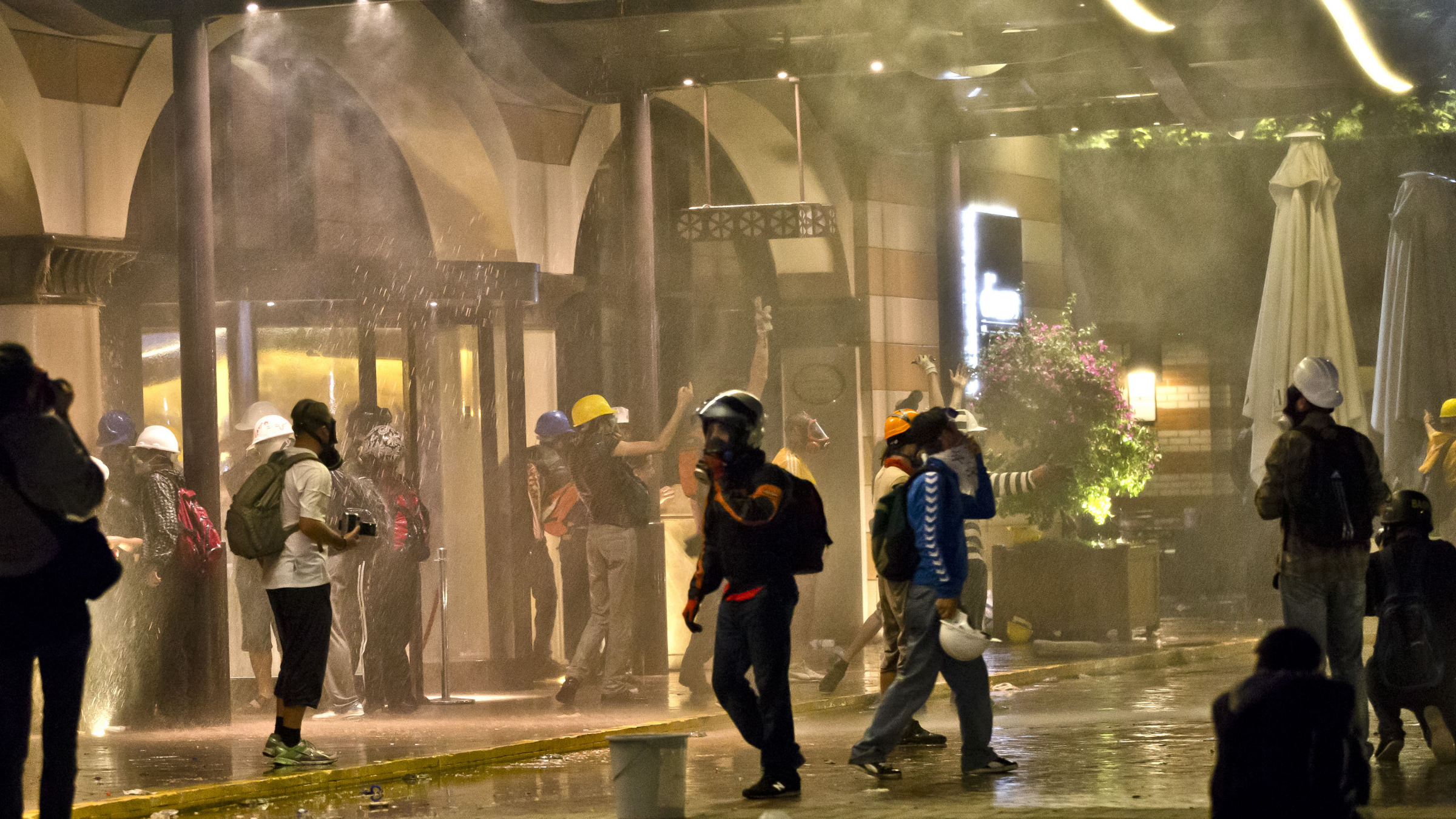 Protesters are engulfed in tear gas and sprayed by water canons at the entrance of the Divan Hotel in Istanbul, Turkey, Saturday, June 15, 2013 after being chased out of Gezi park. Protesters set up barricades and plumes of tear gas rose in Istanbul's streets into the early hours Sunday after Turkish riot police firing tear gas and water cannons cleared out the occupation of a park at the center of the strongest challenge to Prime Minister Recep Tayyip Erdogan's 10-year tenure.(AP Photo/Vadim Ghirda)