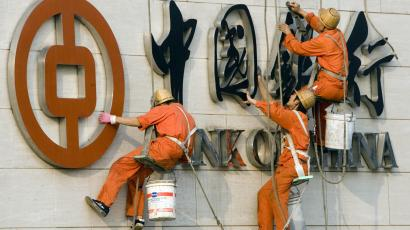 Chinese workers clean the logo of the Bank of China Ltd., China's second biggest commercial bank in Beijing, China, in this Oct. 2, 2006 file photo. Profits are up at China's main state-owned banks, oil companies and other industries as Beijing tries to build global competitors, but management lags far behind foreign rivals, a senior official said Tuesday, Dec. 19, 2006. (AP Photo/Ng Han Guan