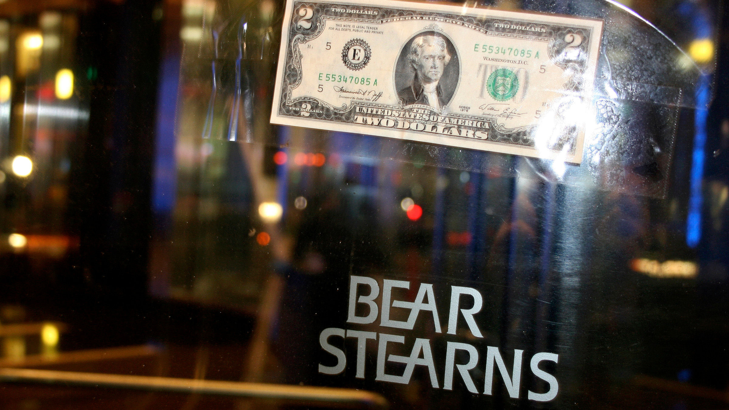A U.S. two dollar bill is taped to the revolving door leading to the Bear Stearns global headquarters in New York March 17, 2008. JPMorgan Chase & Co said on Sunday it would buy stricken rival Bear Stearns for just $2 a share in an all-stock deal that values the U.S. investment bank at the centre of the credit crisis at about $236 million.