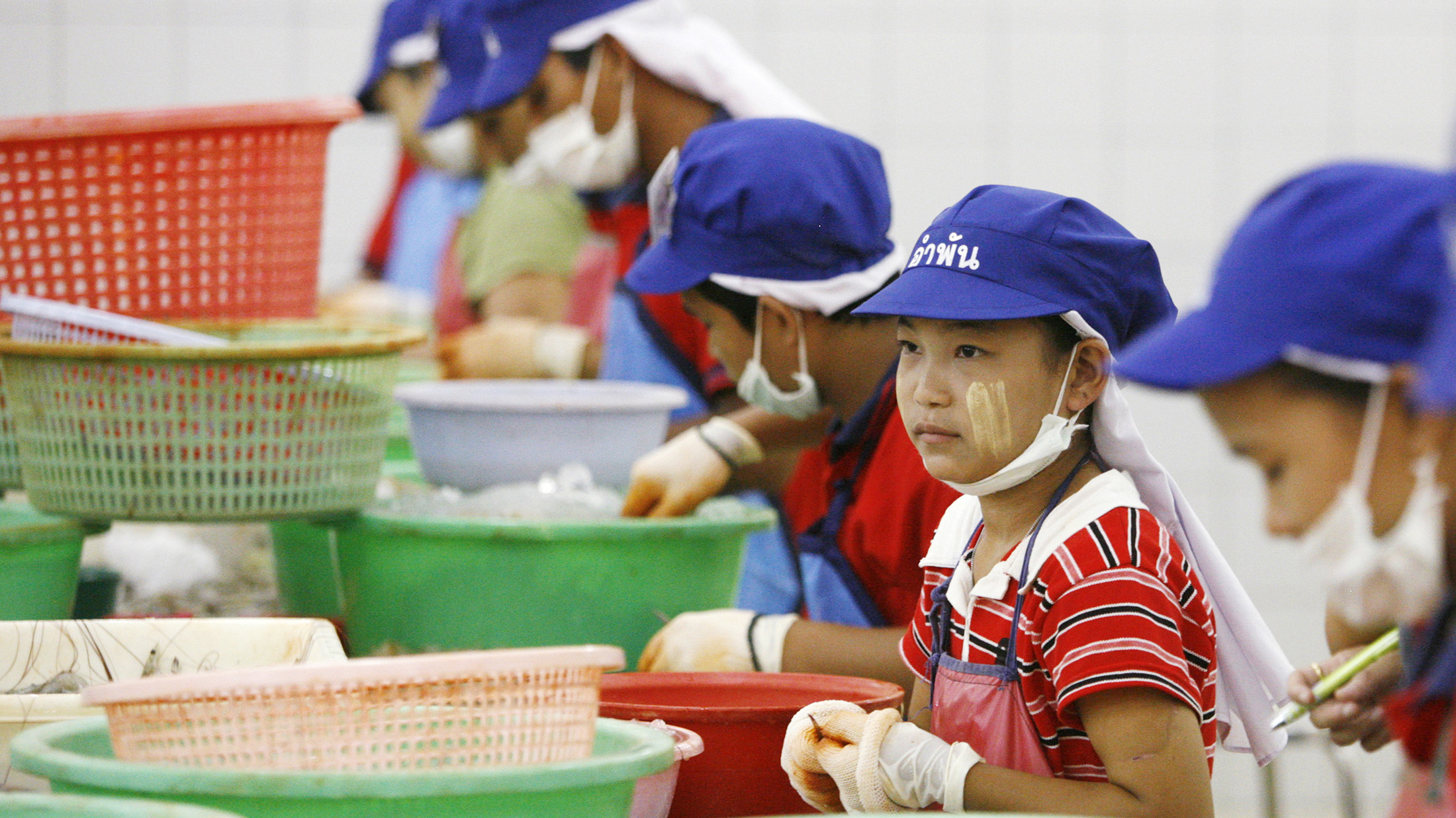 Tae (C), a 13-year-old girl from military-ruled Myanmar, peels shrimp at a factory in Samut Sakhon, nearly 40 km (25 miles) south of Bangkok April 20, 2007. The Labour Rights Promotion Network (LPN), a non-governmental organisation, estimates there are 200,000 Myanmar migrant workers in Samut Sakhon -- of whom only 70,000 are registered legally. To match feature THAILAND-CHILDLABOUR/ REUTERS/Adrees Latif