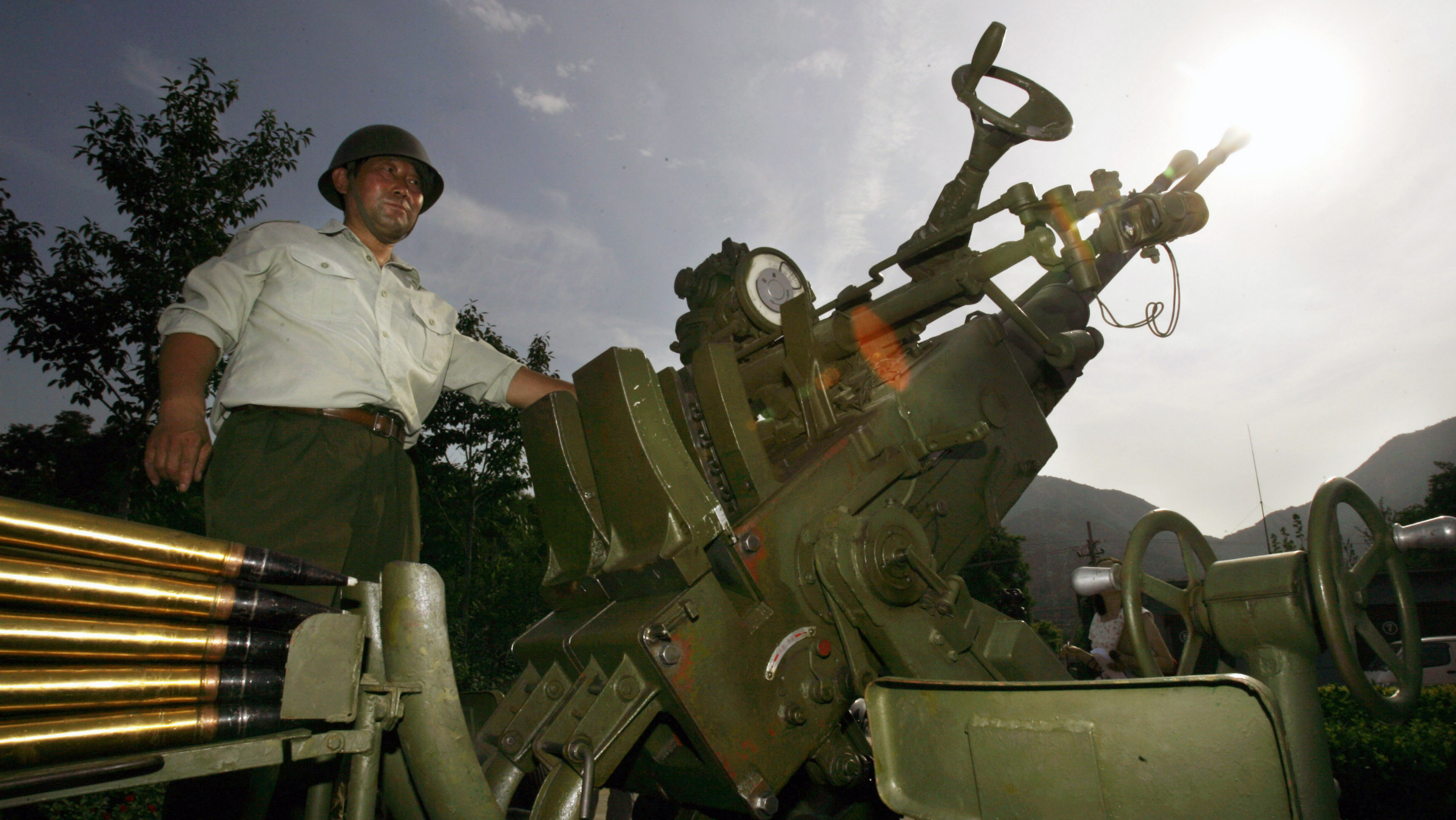 In this July 19, 2007 file picture, an artillery operator stands next to an artillery used to seed clouds to induce rain at a station of the Beijing Meteorological Bureau in Beijing, China. Beijing regularly uses cloud seeding techniques to improve the local weather conditions and the bureau has been tasked to ensure optimum weather conditions for the 2008 Olympic Games.