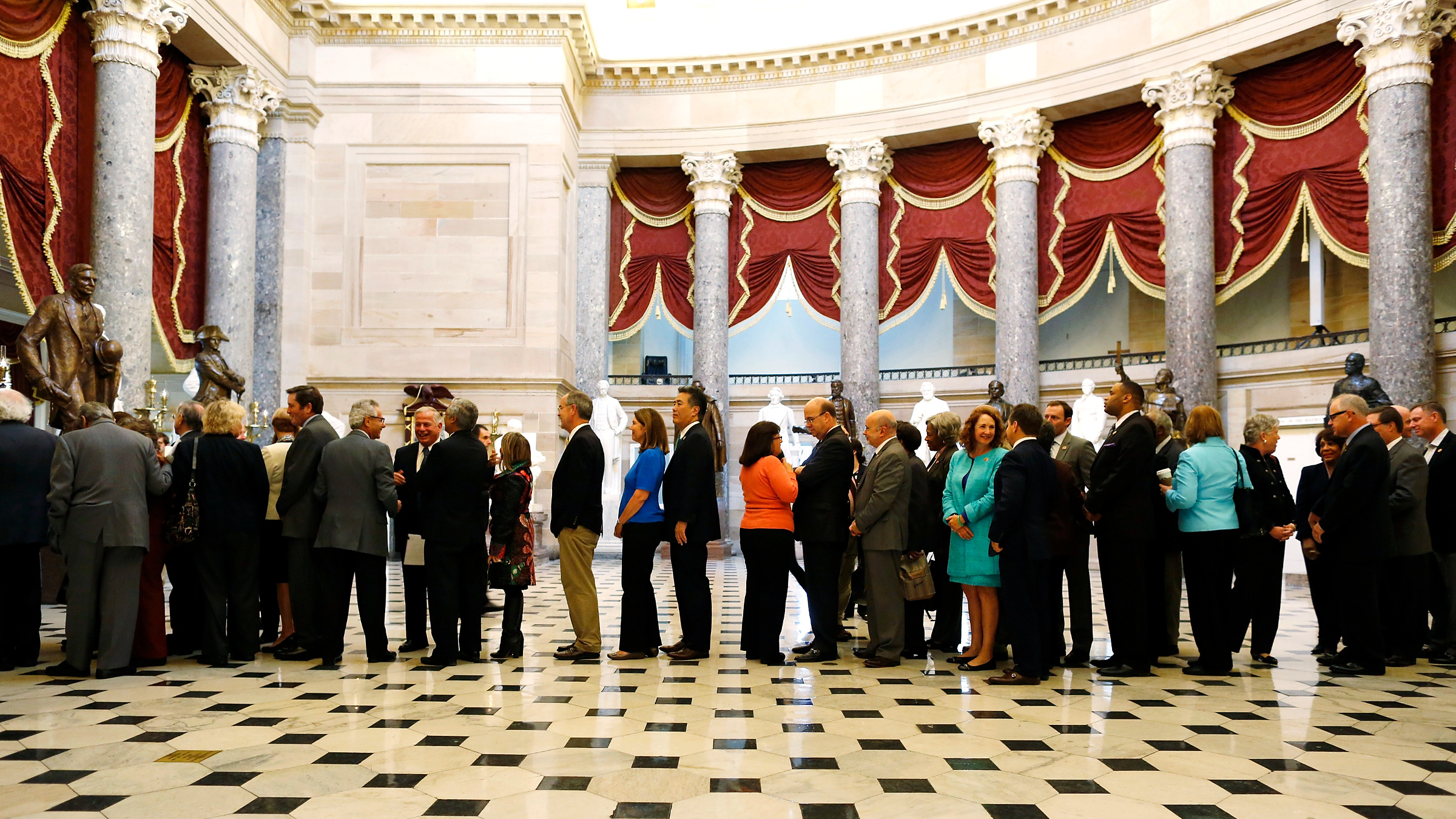 U.S. House Democrats line up single-file to march onto the House Floor for a Saturday session to address the current U.S. government shutdown at the U.S. Capitol in Washington, October 12, 2013. President Barack Obama pressured Republican lawmakers on Saturday to agree to raise the U.S. debt ceiling for longer than they would prefer, as their fiscal impasse dragged into the weekend with five days left to find a deal.