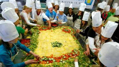 School children prepare a huge slice of bread at the start of a campaign promoting healthy lunch at school in Zwanenburg April 27, 2006. The giant sandwich measures 1.70 by 2.70 meters (5.6 by 8.9 feet). 40,000 school children in the Netherlands will get a free healthy lunch at school.