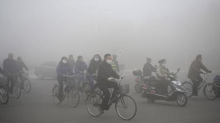 People ride along a street on a smoggy day in Daqing, Heilongjiang province, October 21, 2013. The highest red alert was issued for heavy smog in several cities in Heilongjiang province on Monday, according to Xinhua News Agency. The second day of heavy smog with a PM 2.5 index has forced the closure of schools and highways, exceeding 500 micrograms per cubic meter on Monday morning in downtown Harbin, the provincial capital. REUTERS/Stringer