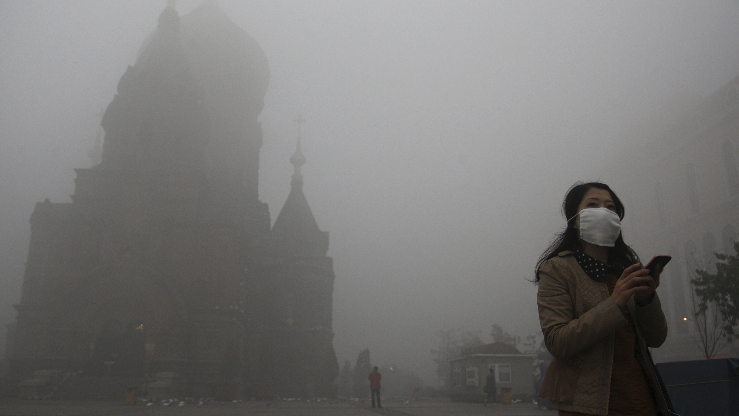 A woman wearing a mask checks her mobile phone during a smoggy day on the square in front of Harbin's landmark San Sophia church, in Heilongjiang province October 21, 2013. The second day of heavy smog with a PM 2.5 index has forced the closure of schools and highways, exceeding 500 micrograms per cubic meter on Monday morning in downtown Harbin, according to Xinhua News Agency. REUTERS/Stringer