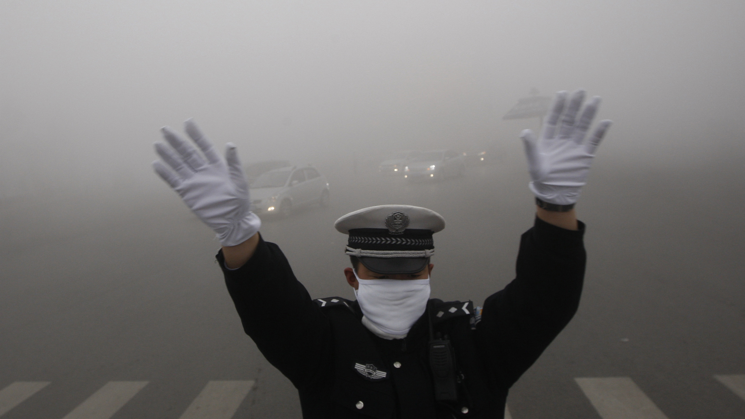 A traffic policeman signals to drivers during a smoggy day in Harbin, Heilongjiang province, October 21, 2013. The second day of heavy smog with a PM 2.5 index has forced the closure of schools and highways, exceeding 500 micrograms per cubic meter on Monday morning in downtown Harbin, according to Xinhua News Agency. REUTERS/China Daily