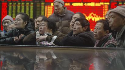 Investors listen to a lecture in front of an electronic board showing stock information at a brokerage house in Shanghai January 27, 2010. China's key stock index slipped 1.09 percent to a three-month closing low on Wednesday, with bank shares weaker on concerns over tightening liquidity despite upbeat earnings estimates from two major lenders. REUTERS/Stringer